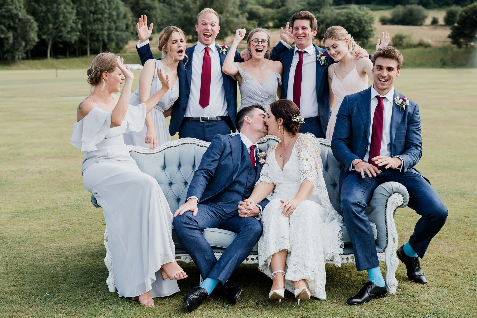 bridal party cheer as bride and groom kiss