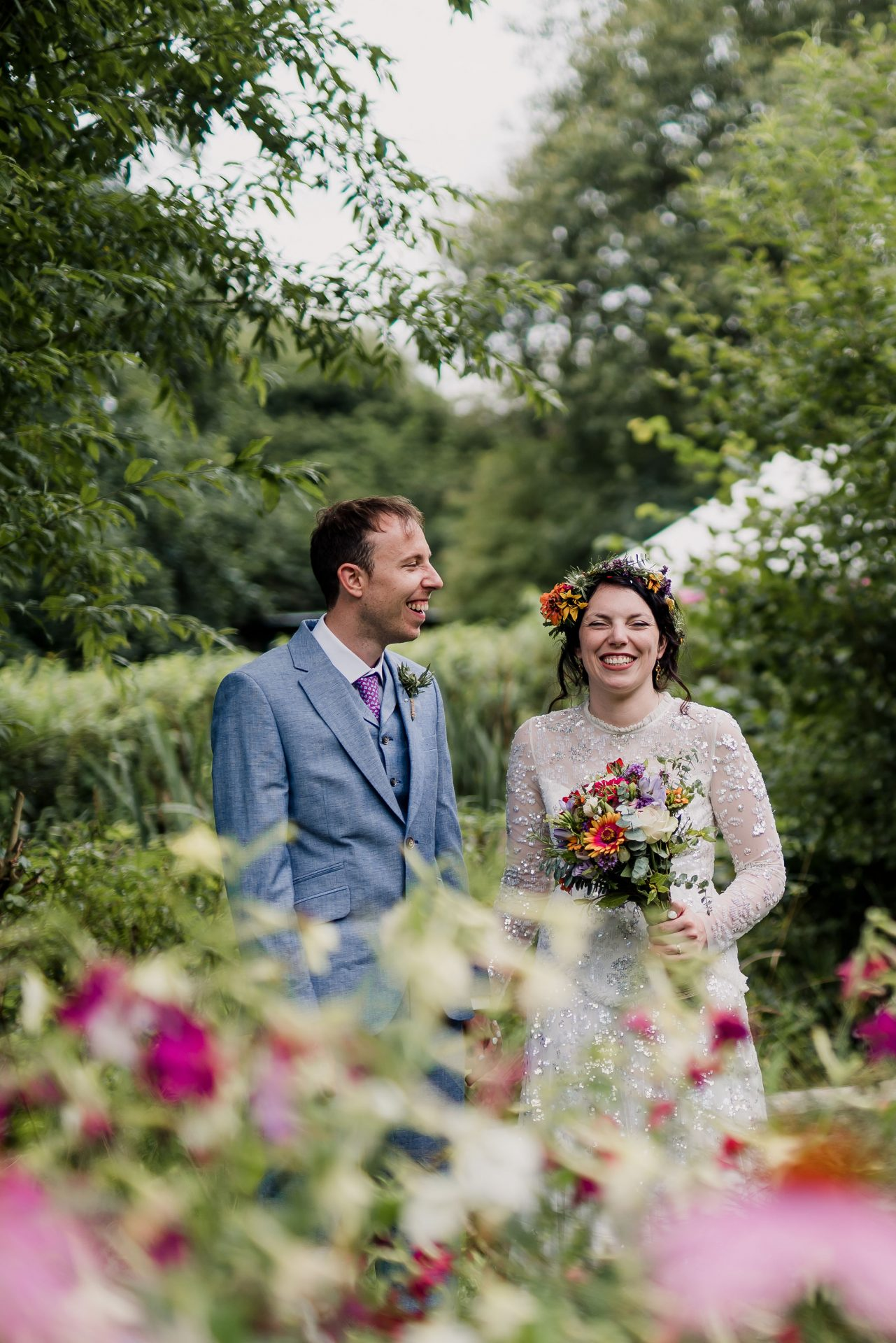 bride and groom laughing in the flowers