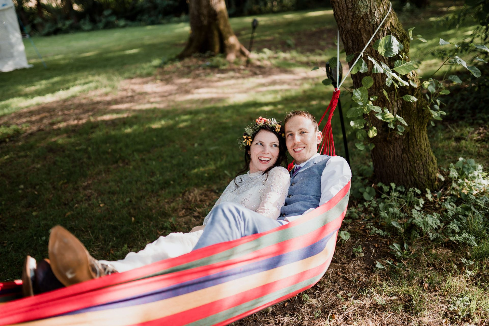 bride and groom laughing in colourful hammock