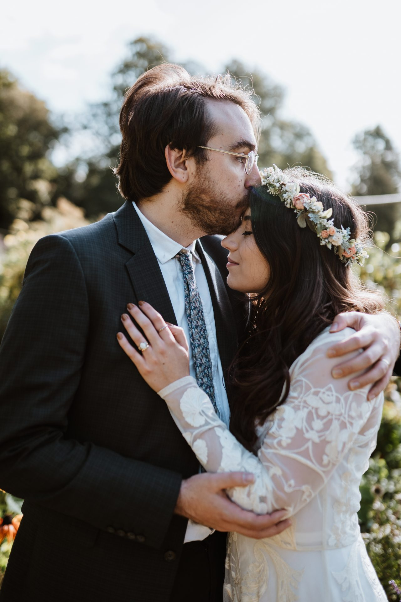 groom kisses bride's forehead with floral crown