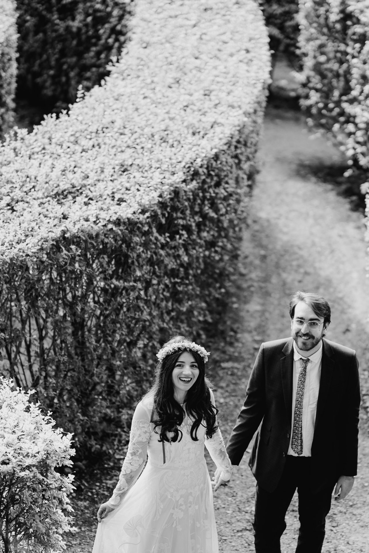 bride and groom holding hands in a maze looking up at the camera