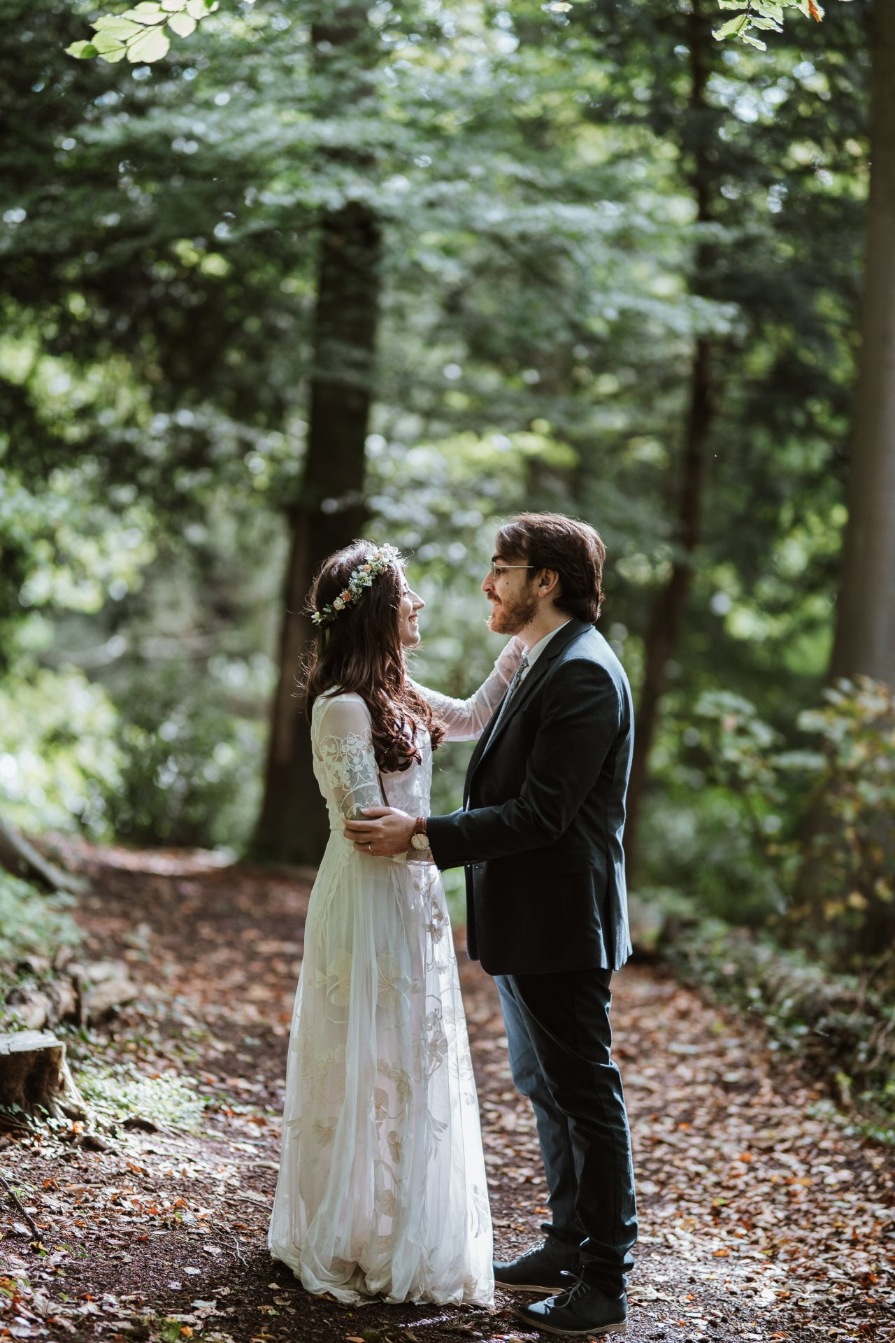 boho bride and groom look at each other in the forest