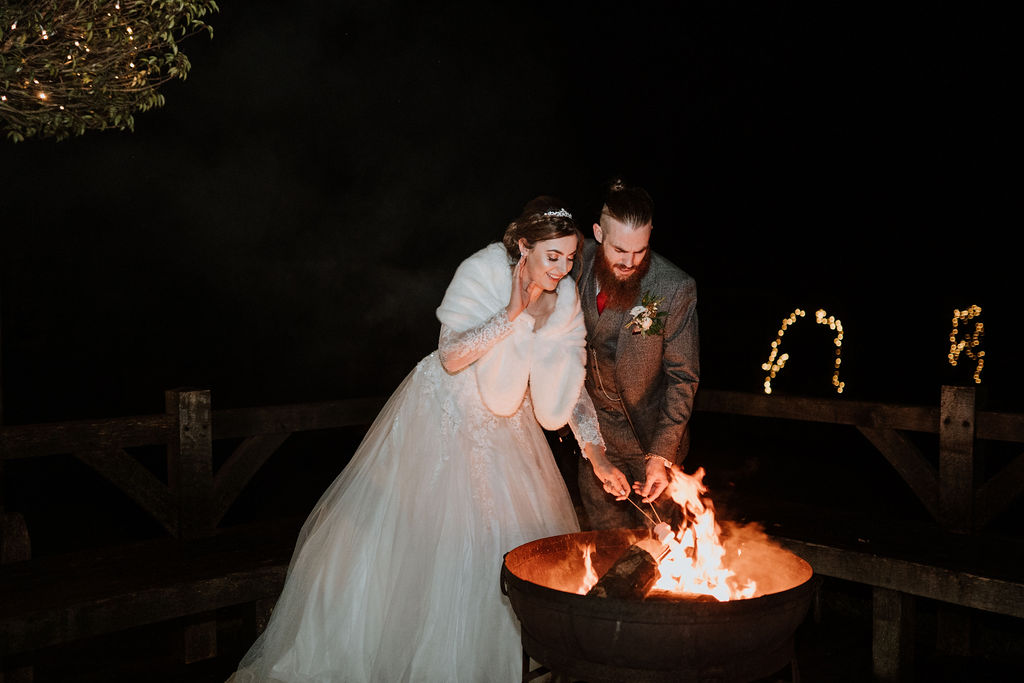bride and groom toasting marshmallows firepit