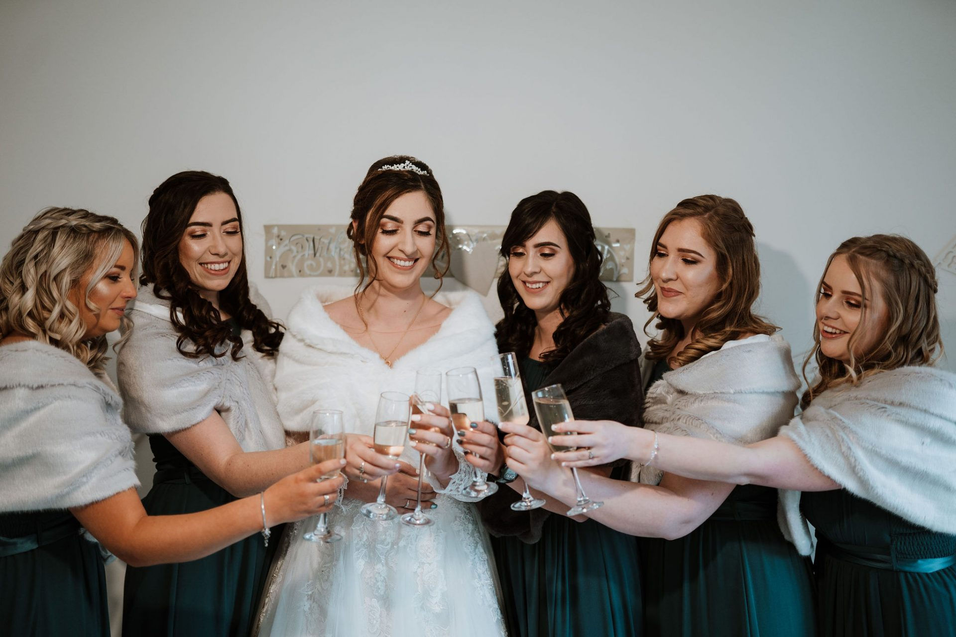 bridesmaids and brides toasting champagne glasses
