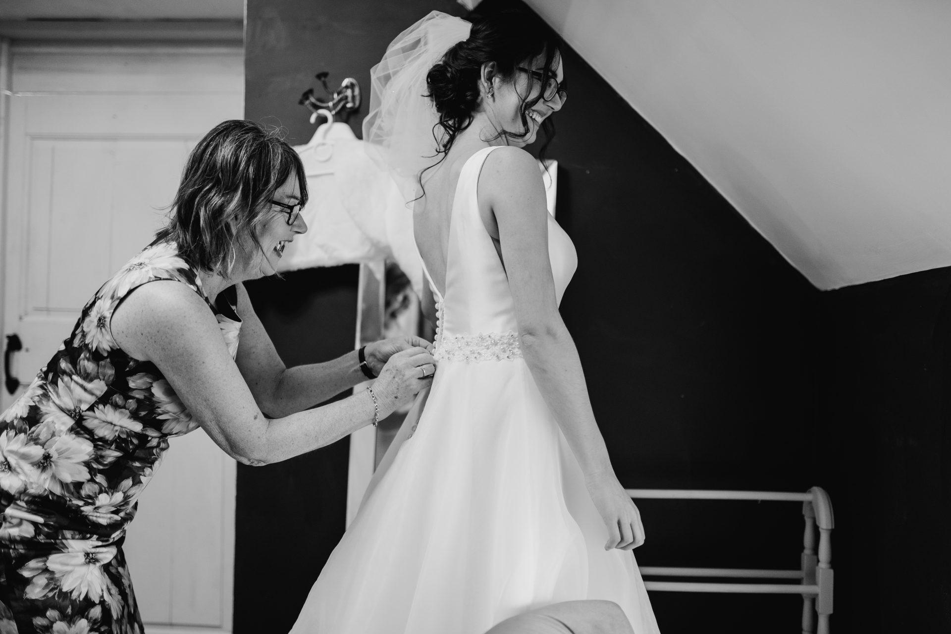 mother doing up brides wedding dress