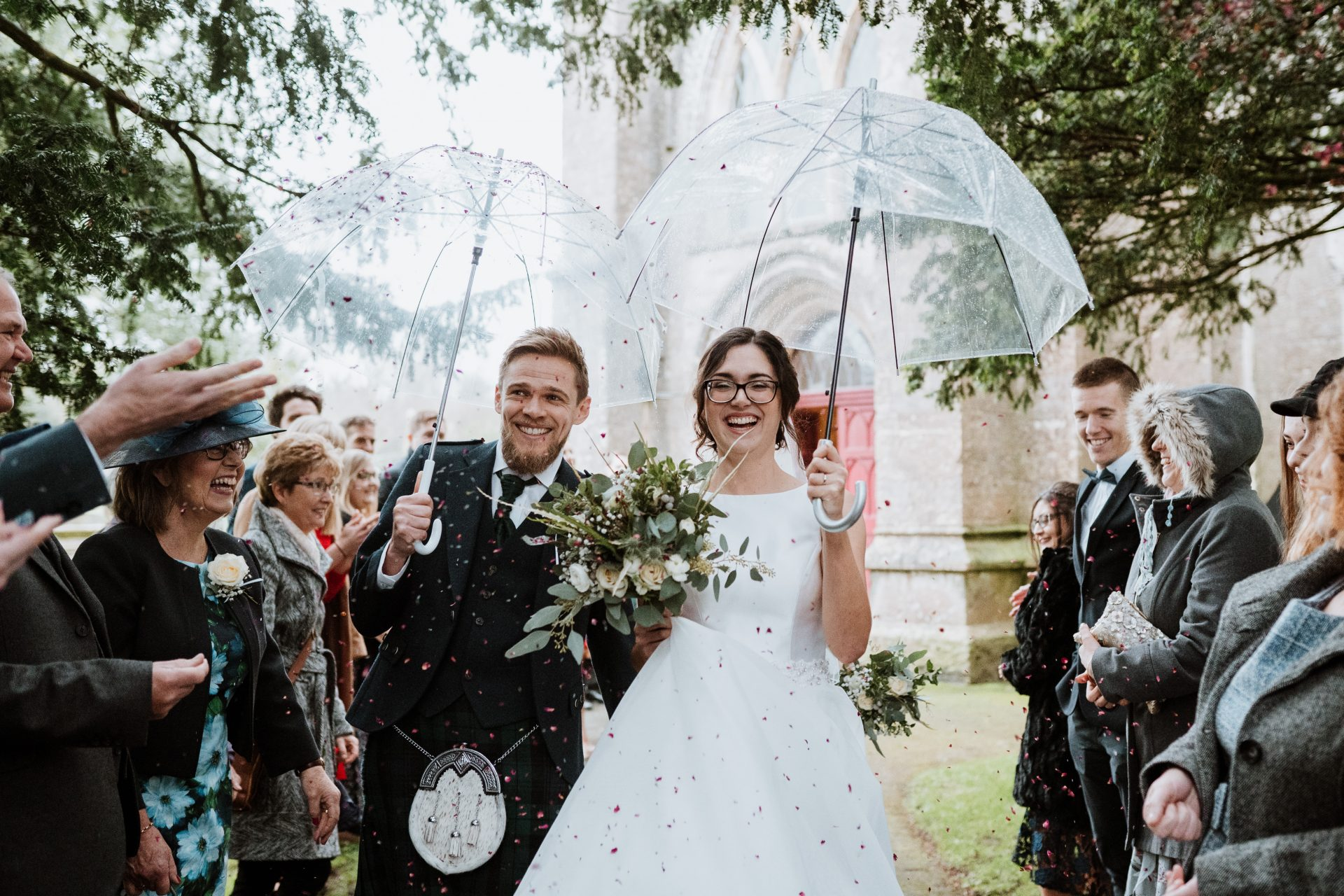 bride and groom walk through the confetti tunnel under umbrellas