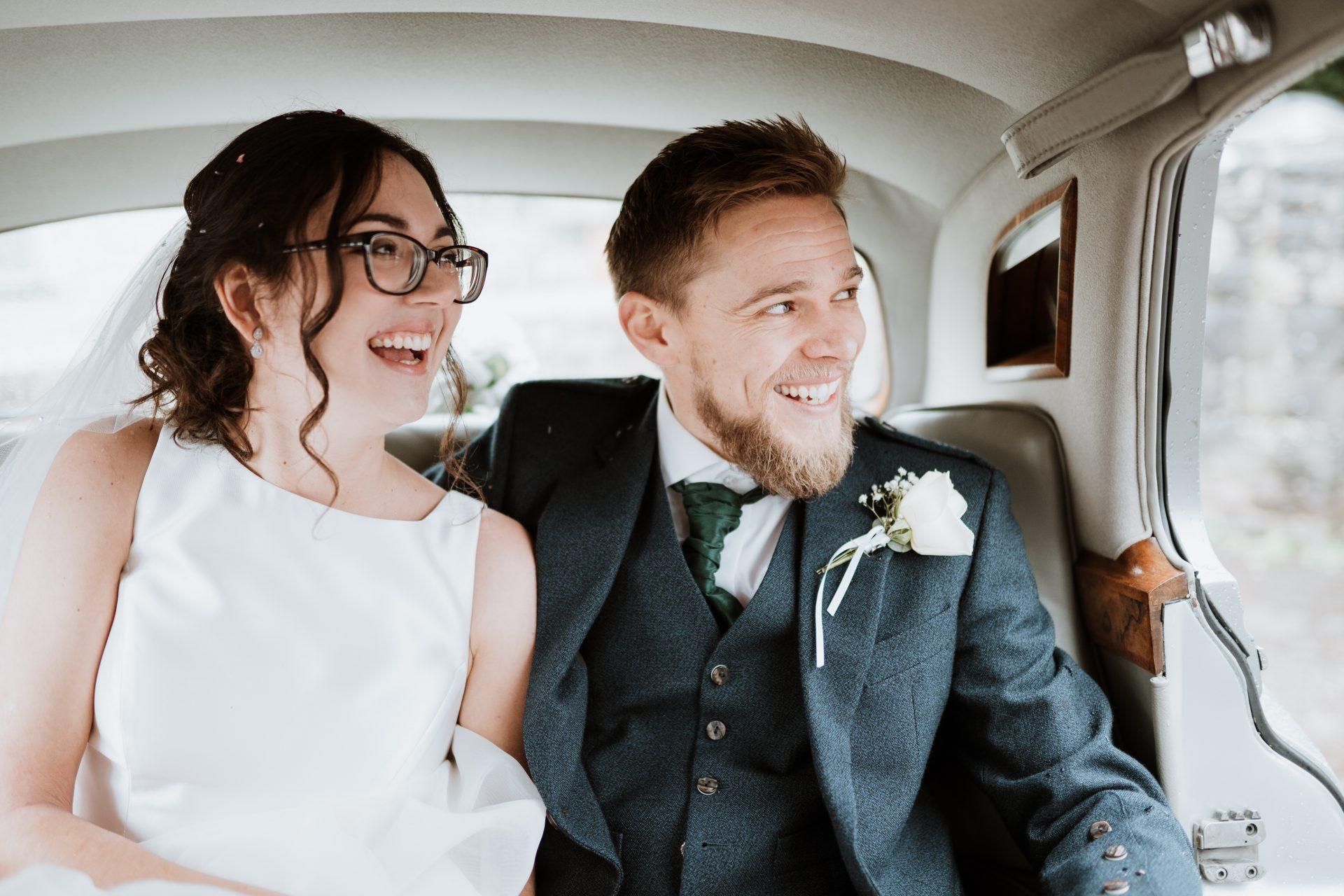 bride and groom laugh in vintage car