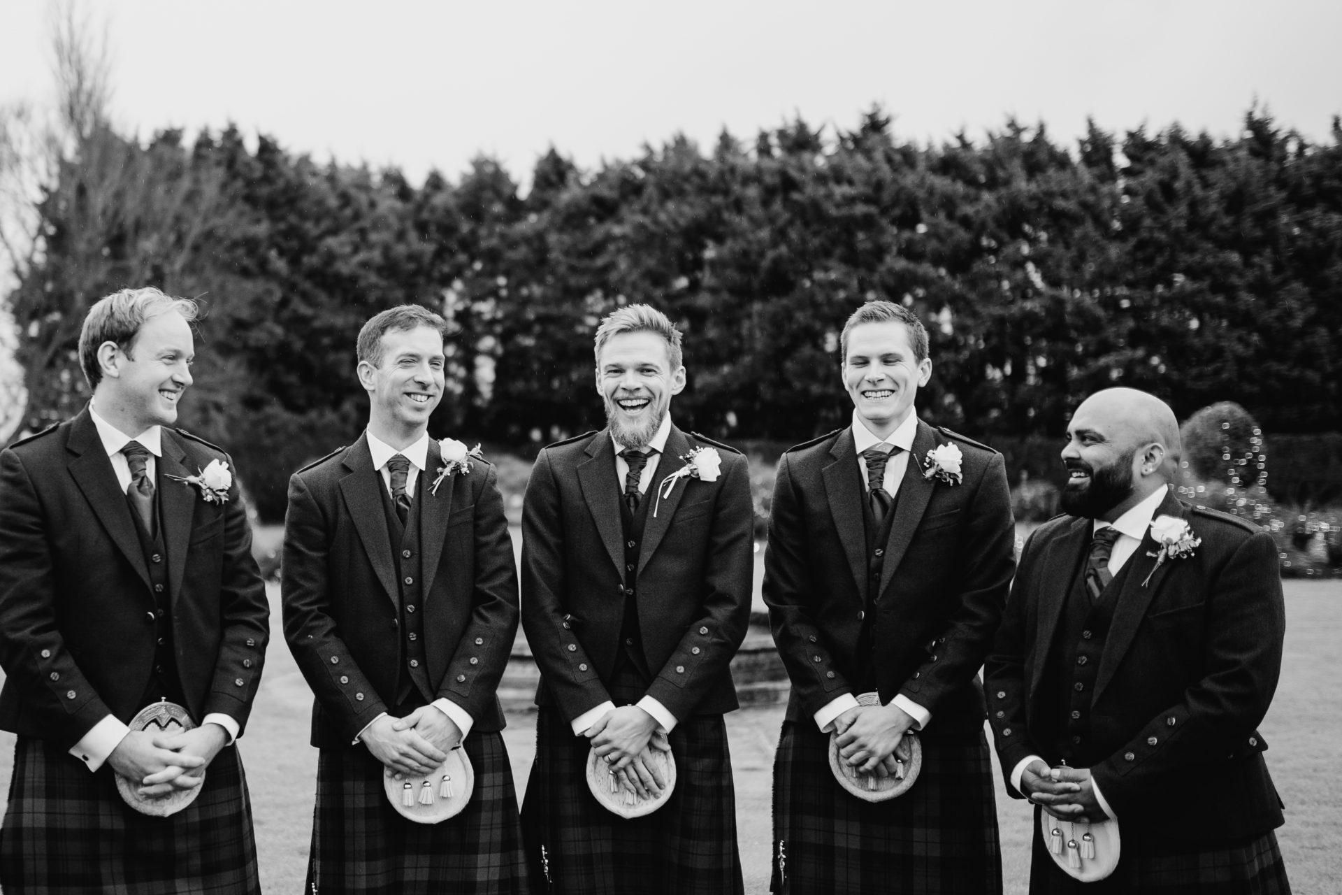 groomsmen and groom laughing in kilts