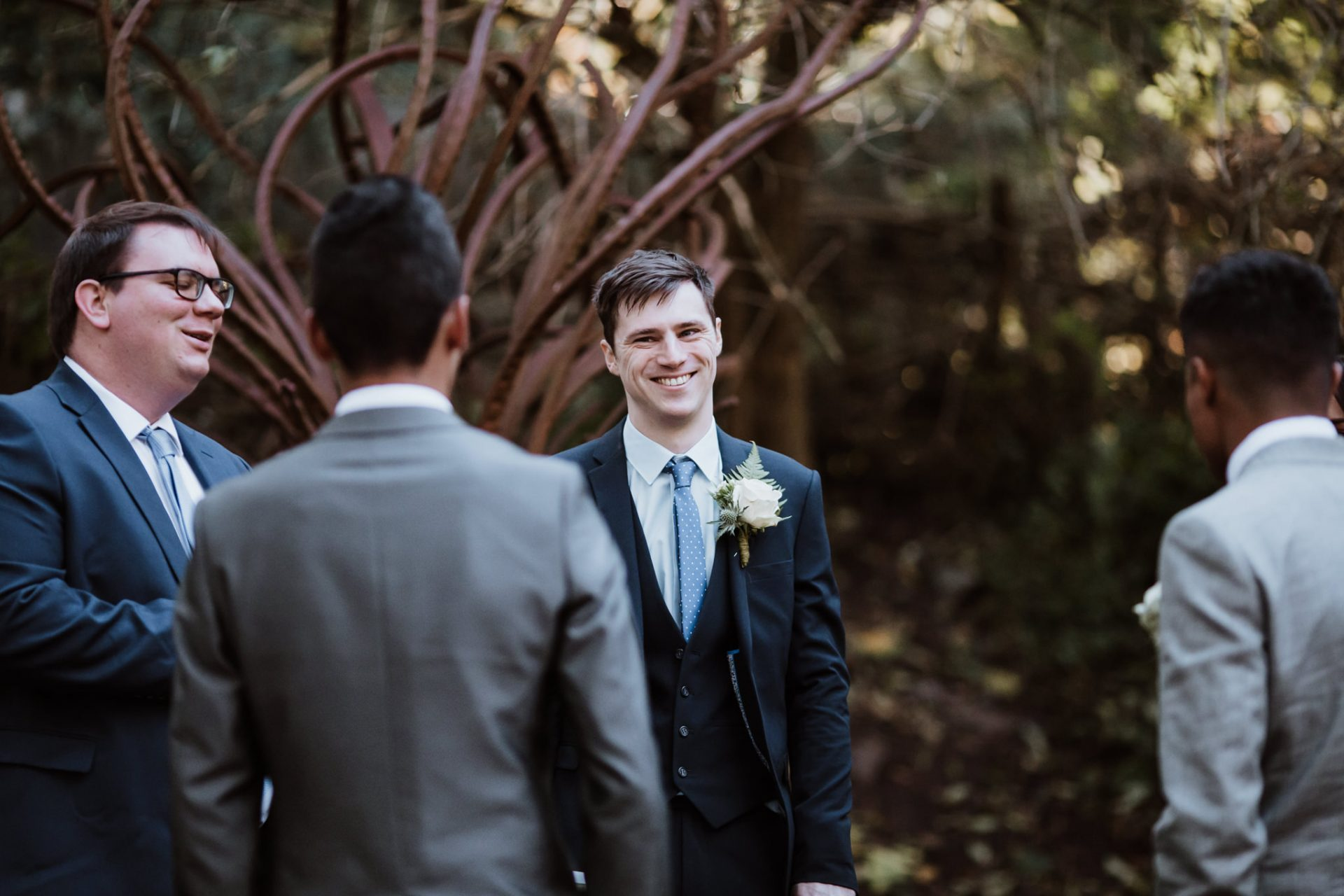 groom laughing with guests before ceremony