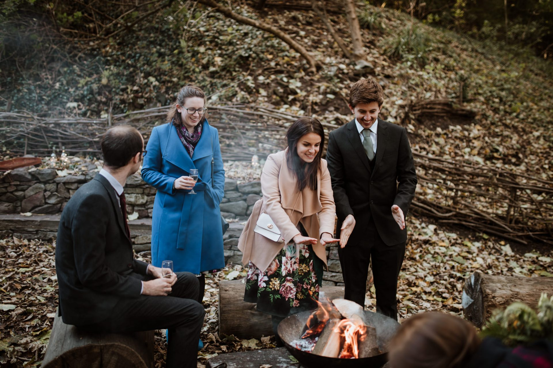 guests warming hands around a fire pit