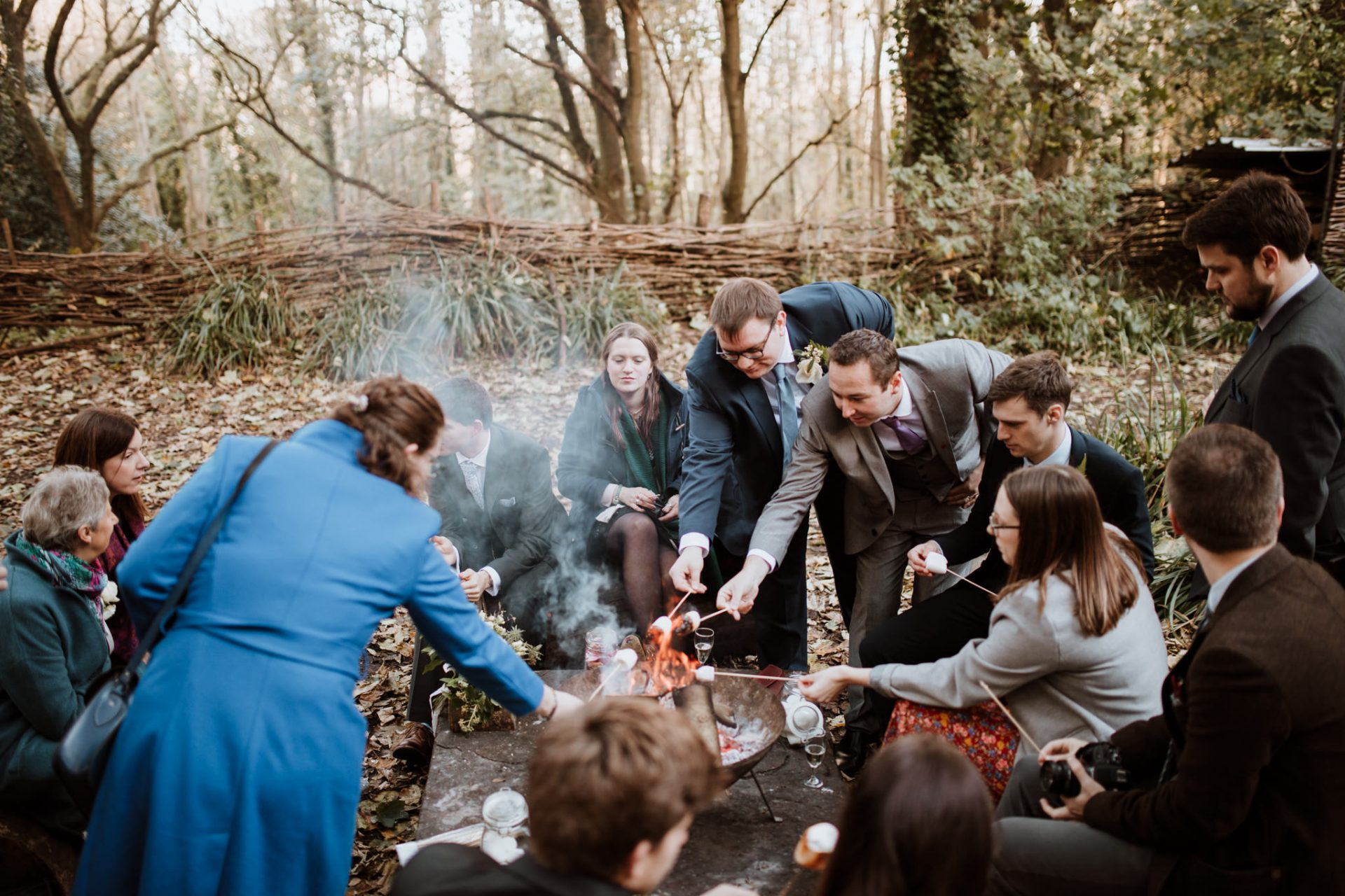 wedding guests toasting marshmallows around a fire pit