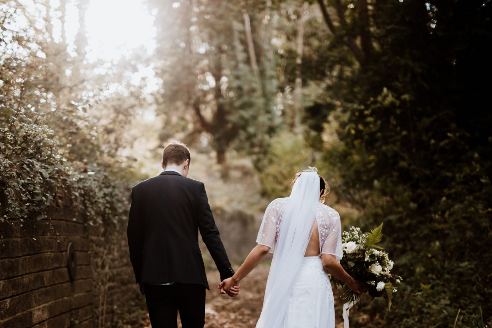 bride and groom arnos vale wedding walking through the woods