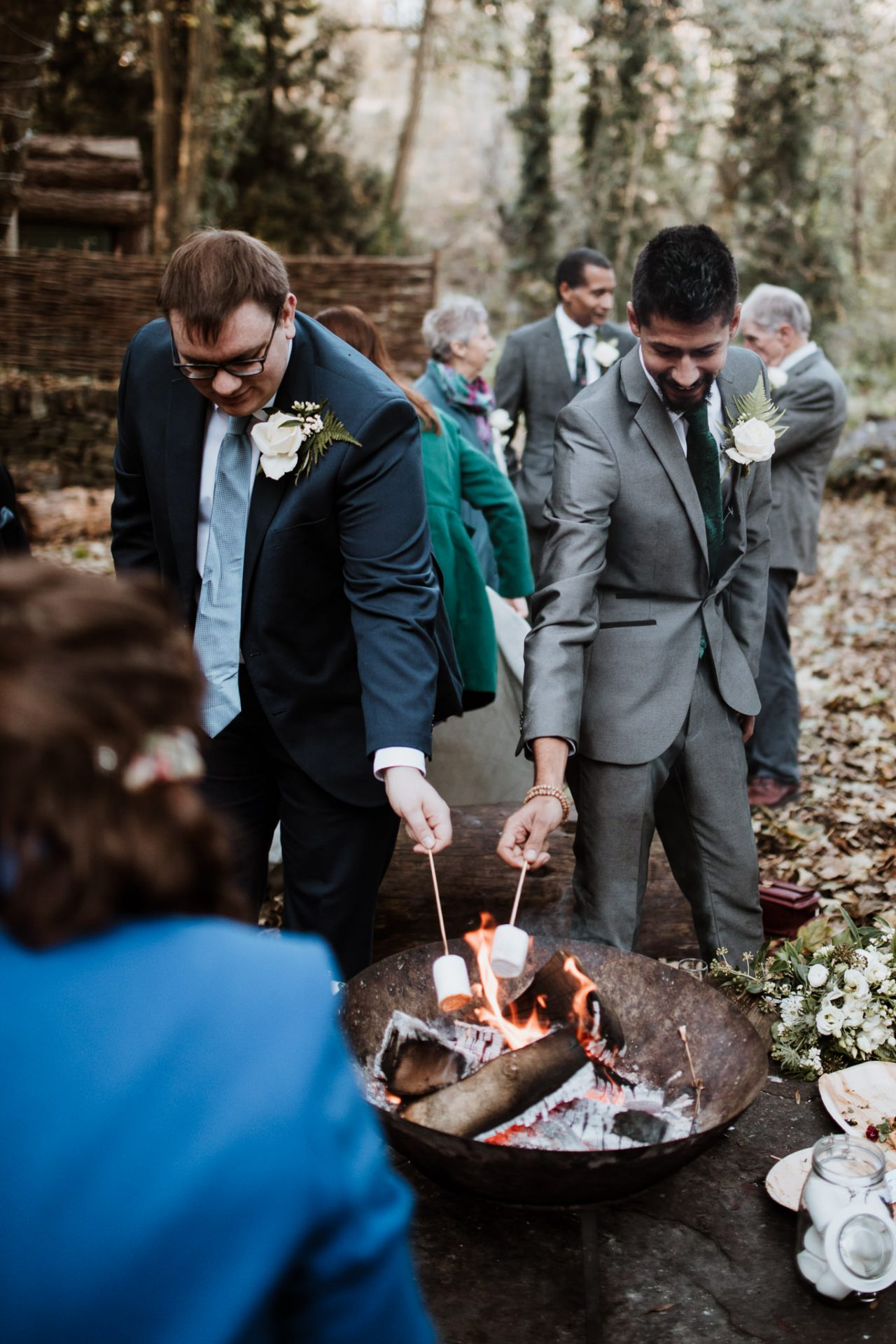 wedding guests toasting marshmallows on fire pit