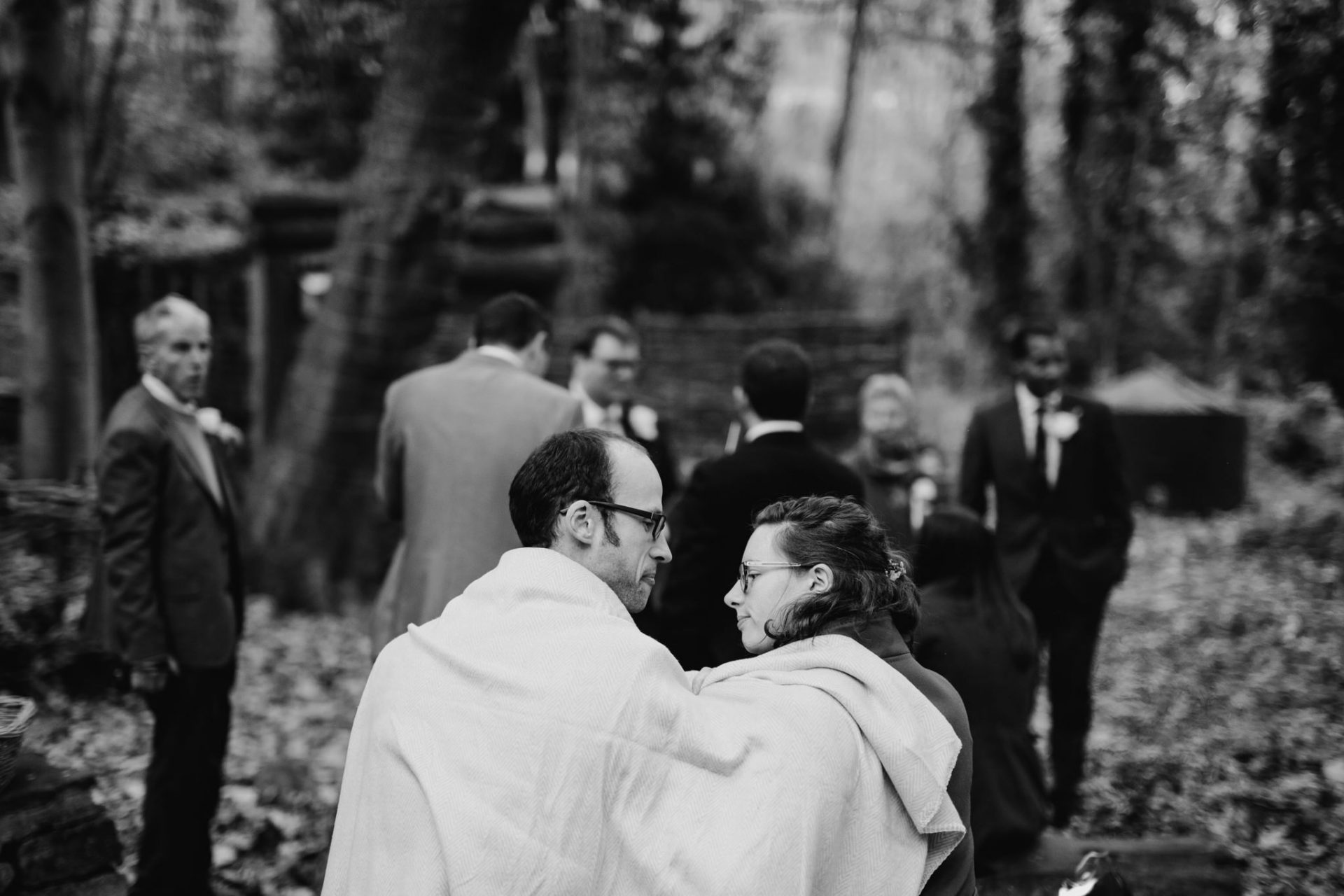 wedding guests share scarf keeping warm