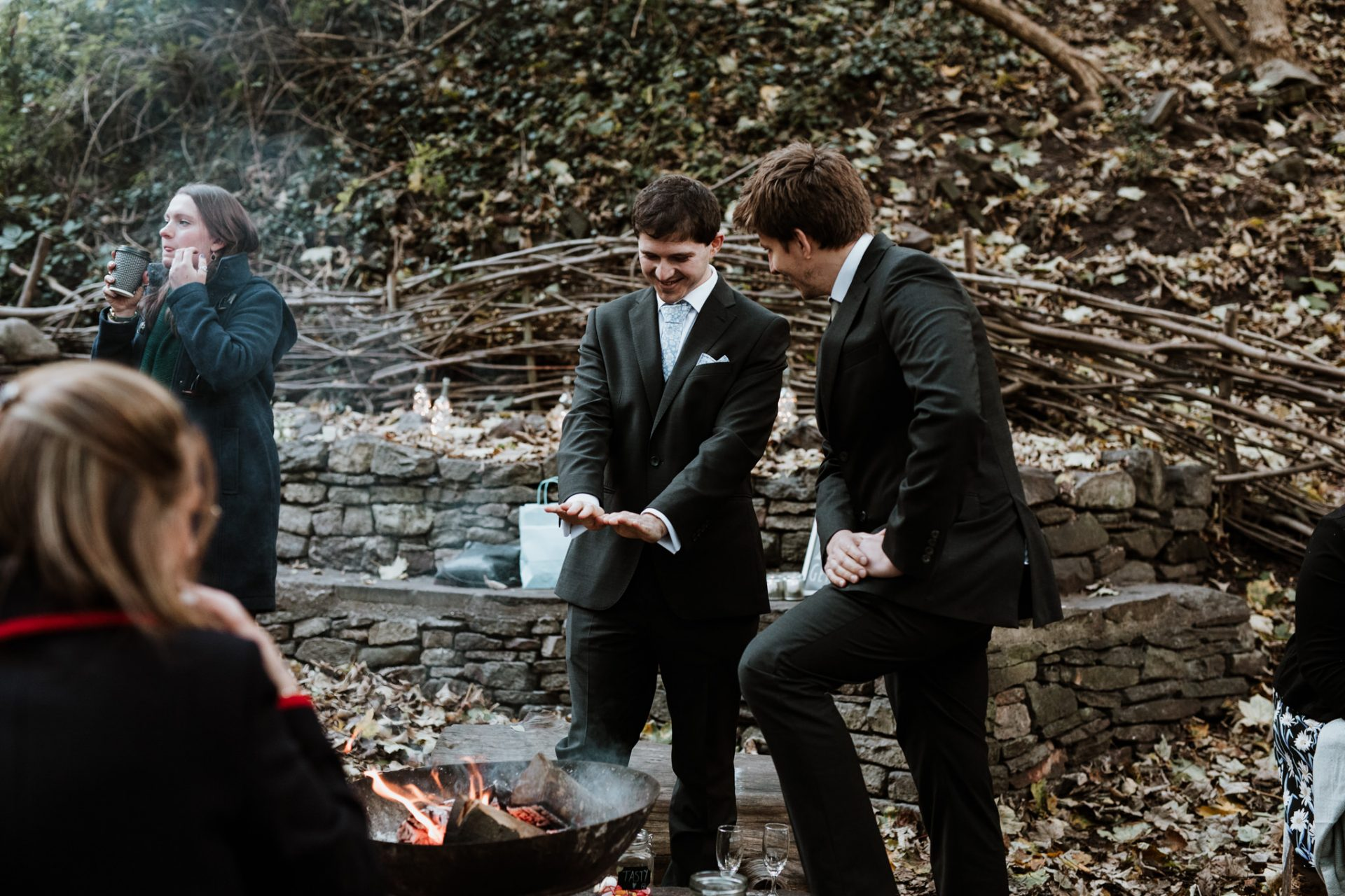 wedding guests warming hands fire pit candid wedding photography