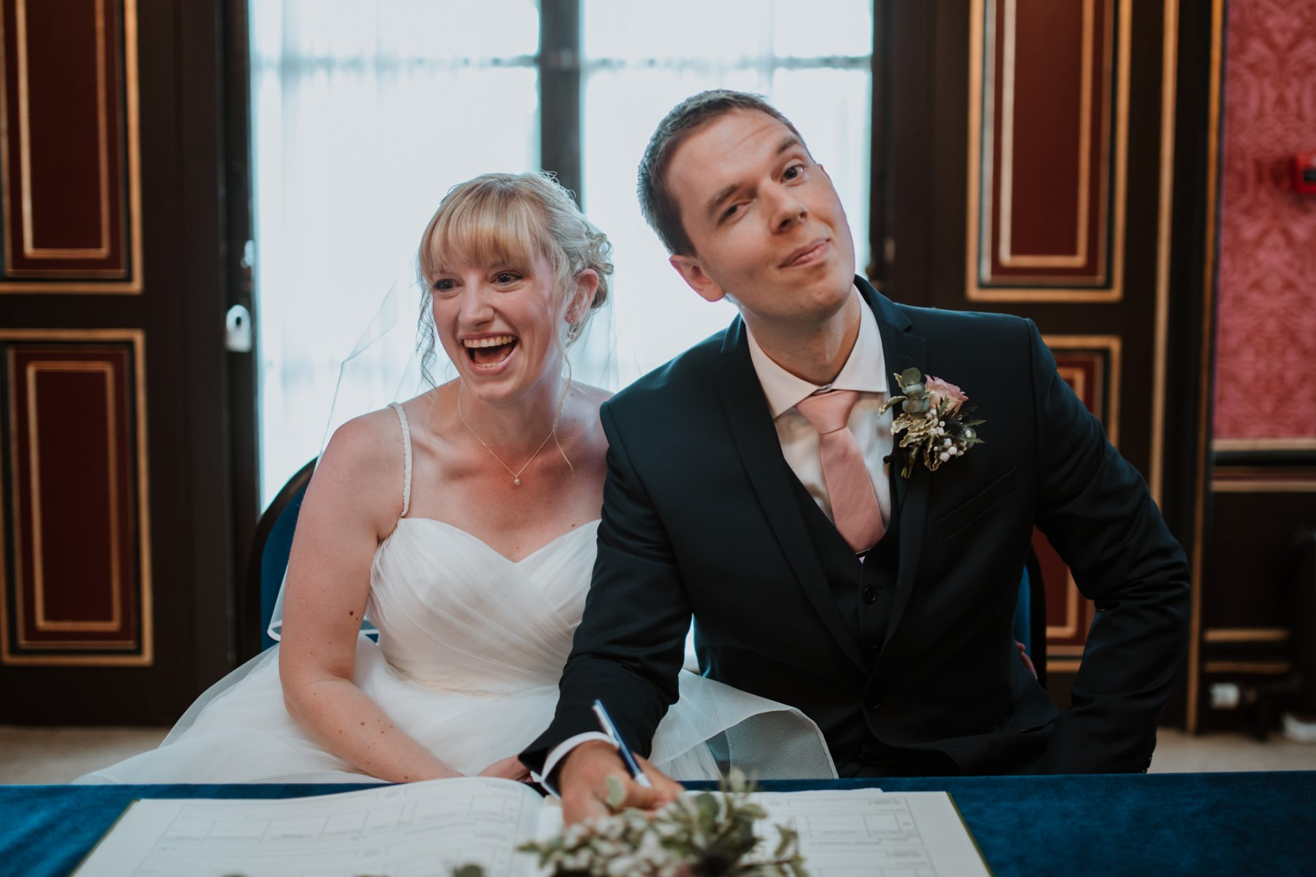 bride and groom jokingly signing the register