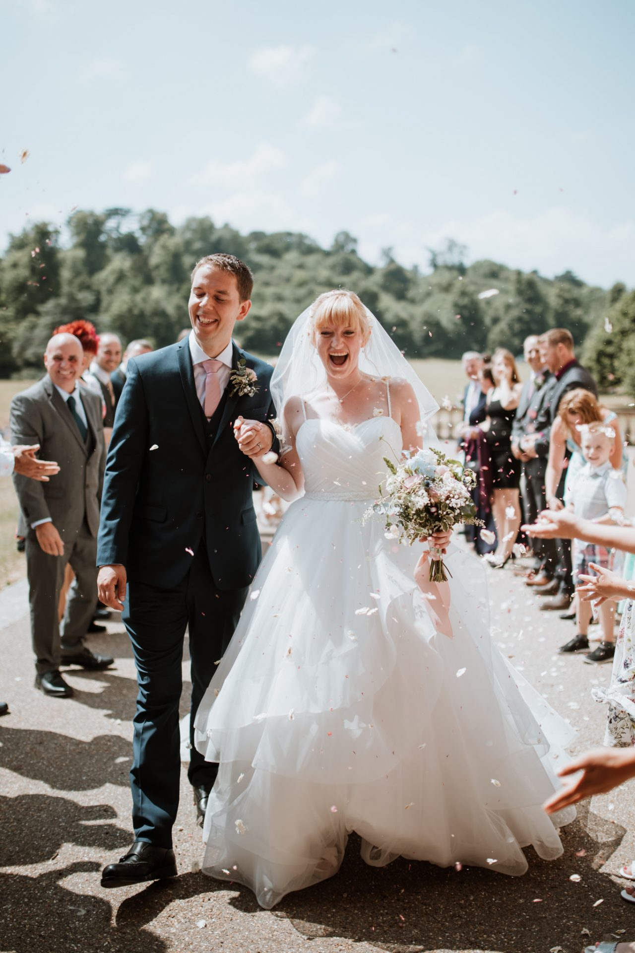 bride and groom walk through confetti tunnel outside blaise castle house museum