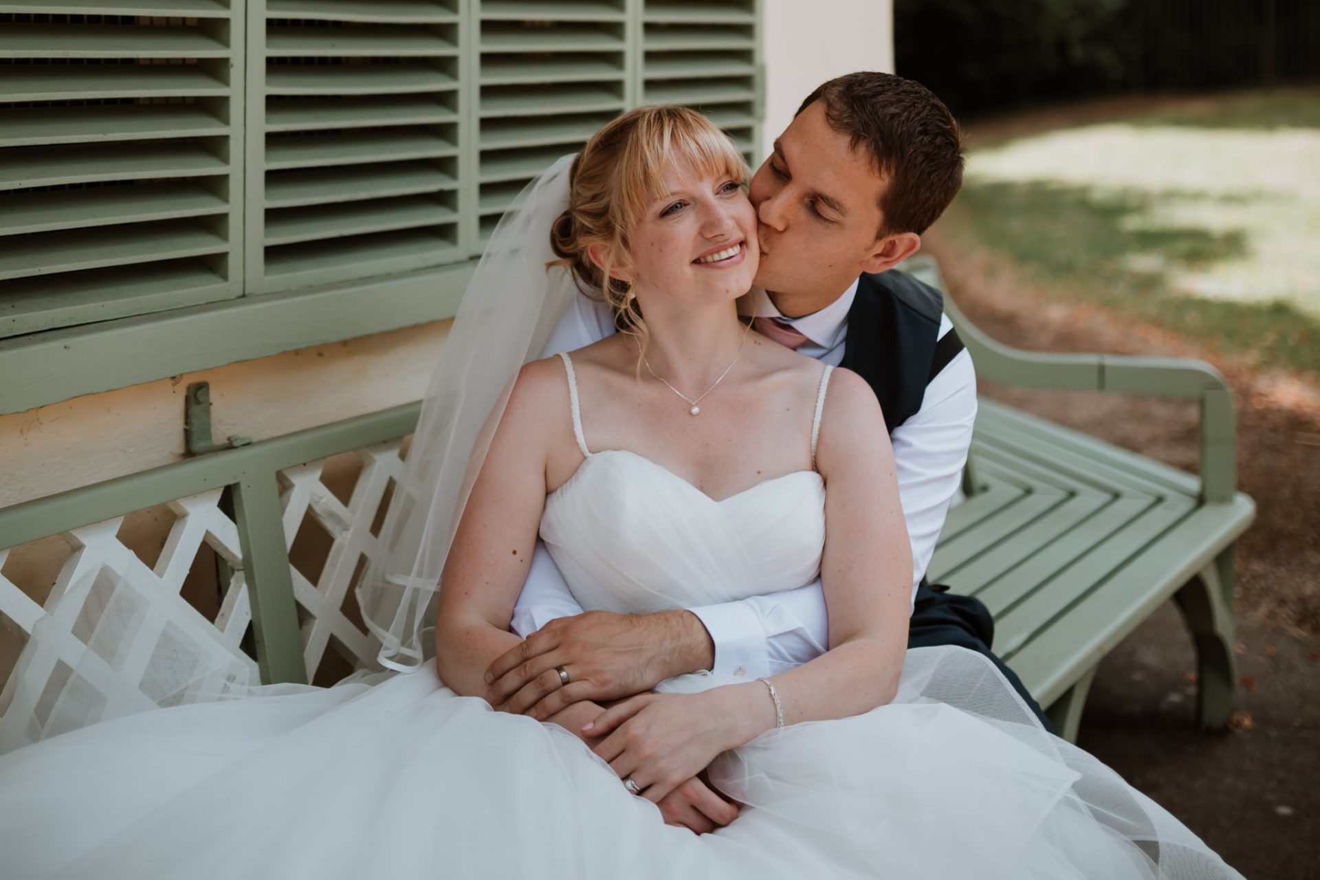 bride and groom sat on bench outside rustic house