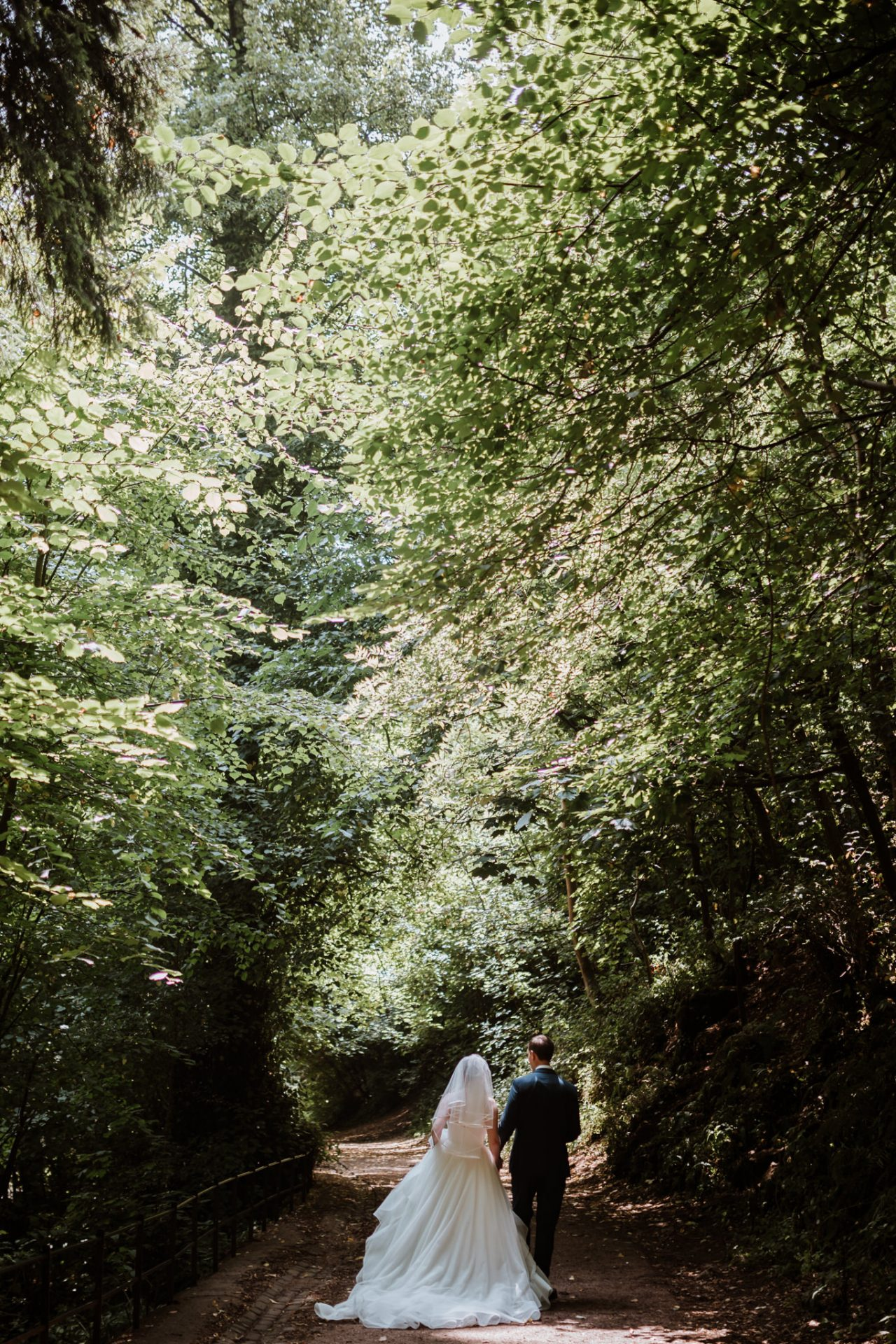 bride and groom walking through the forest dappled lighting