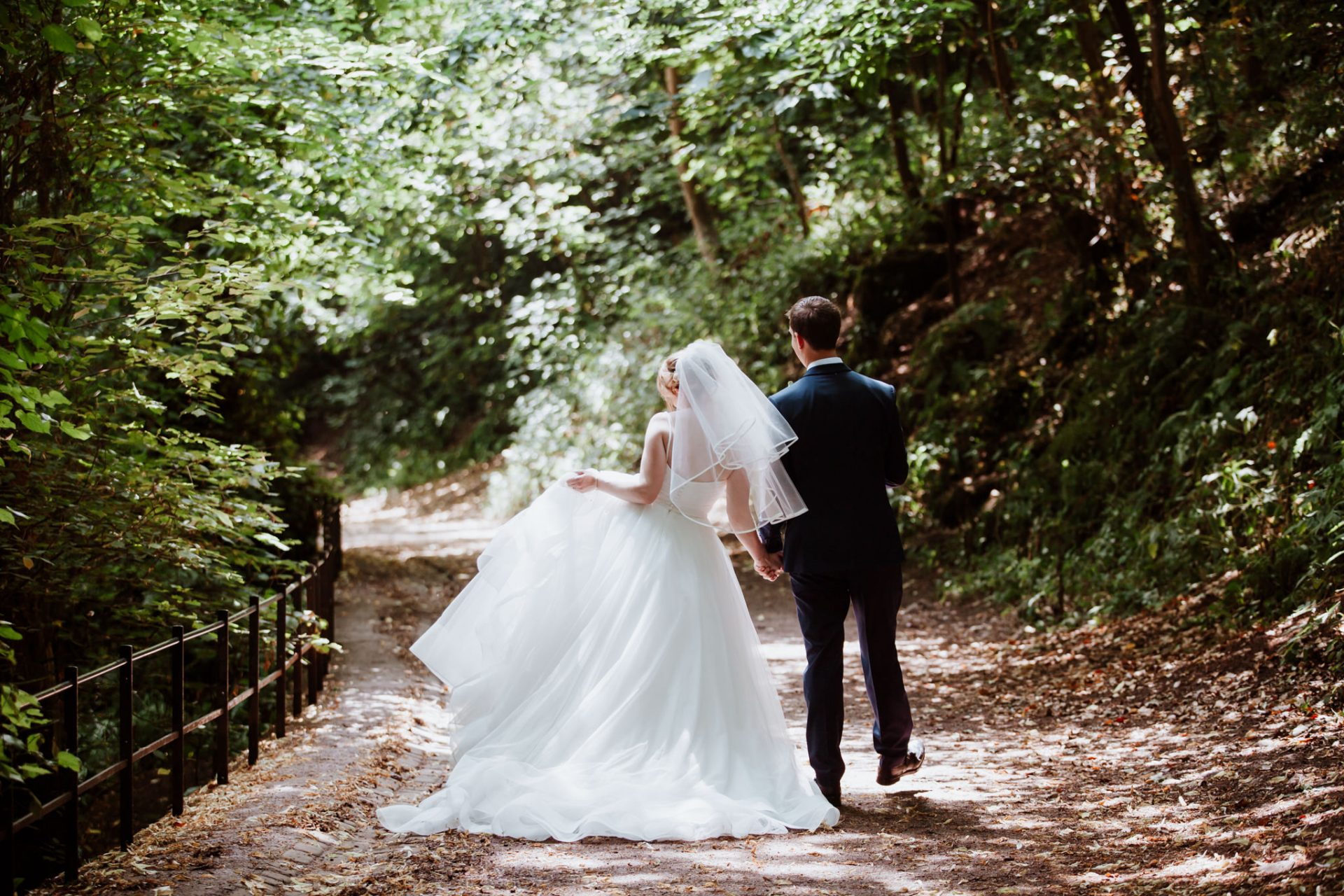 bride and groom dancing through the forest path