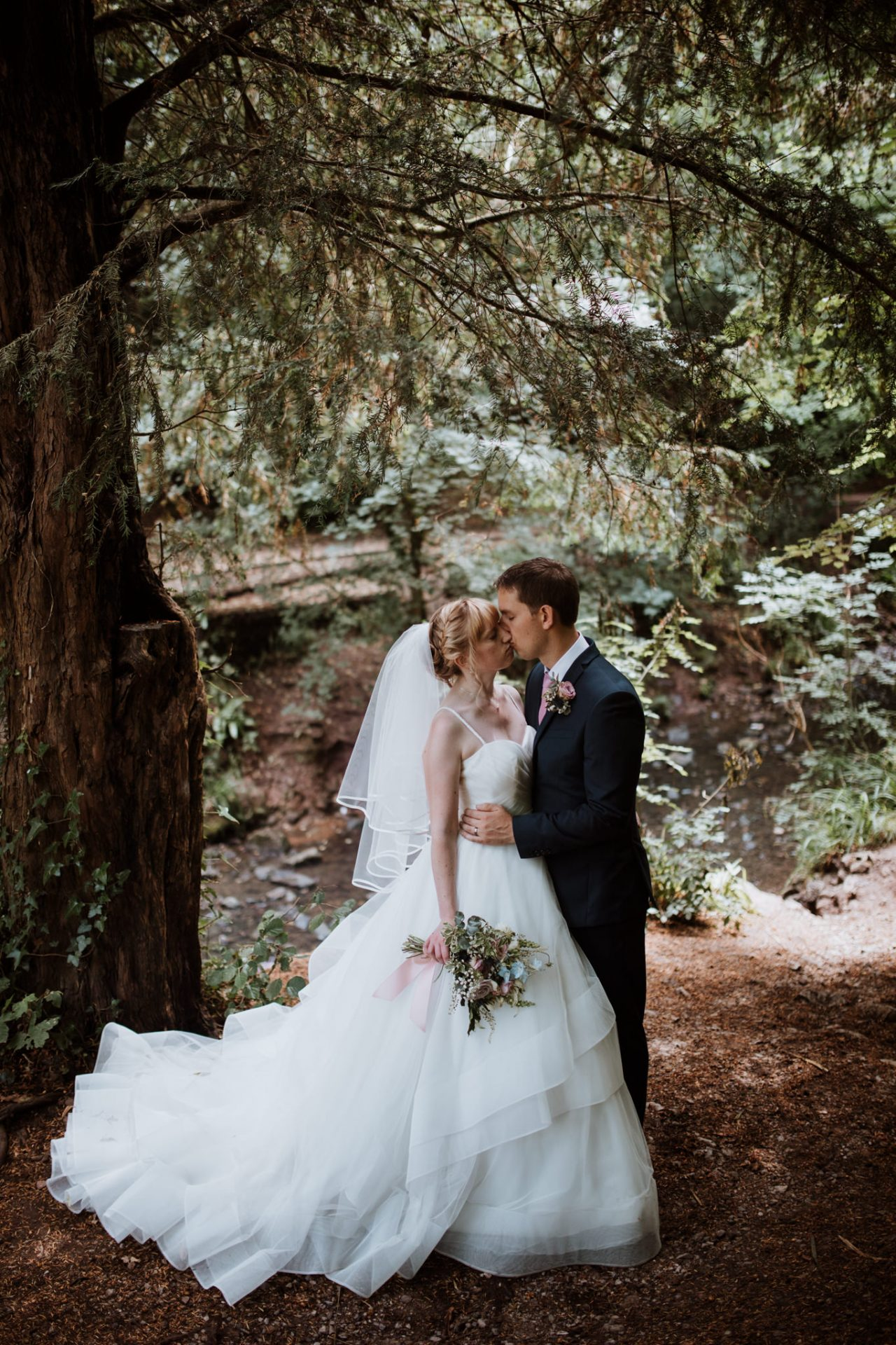 bride and groom kissing underneath tree by the river