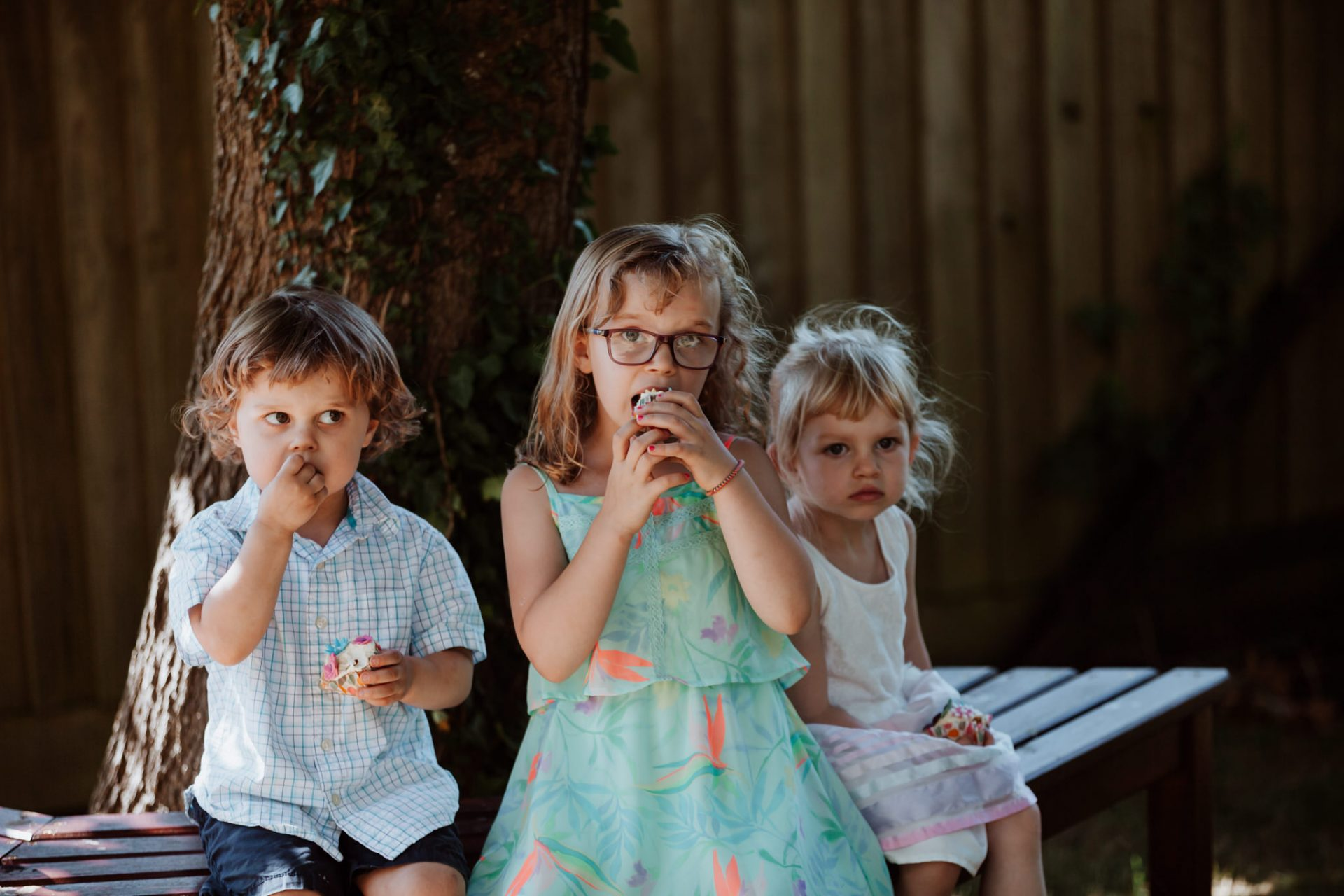 children eating cupcakes under a tree