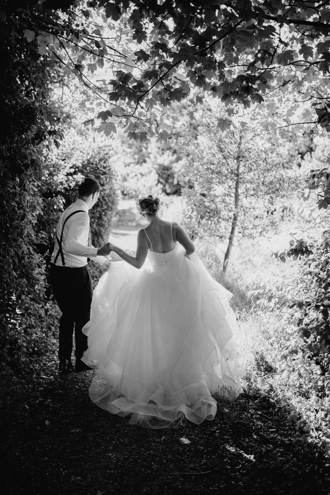 bride and groom holding hands walking down a path