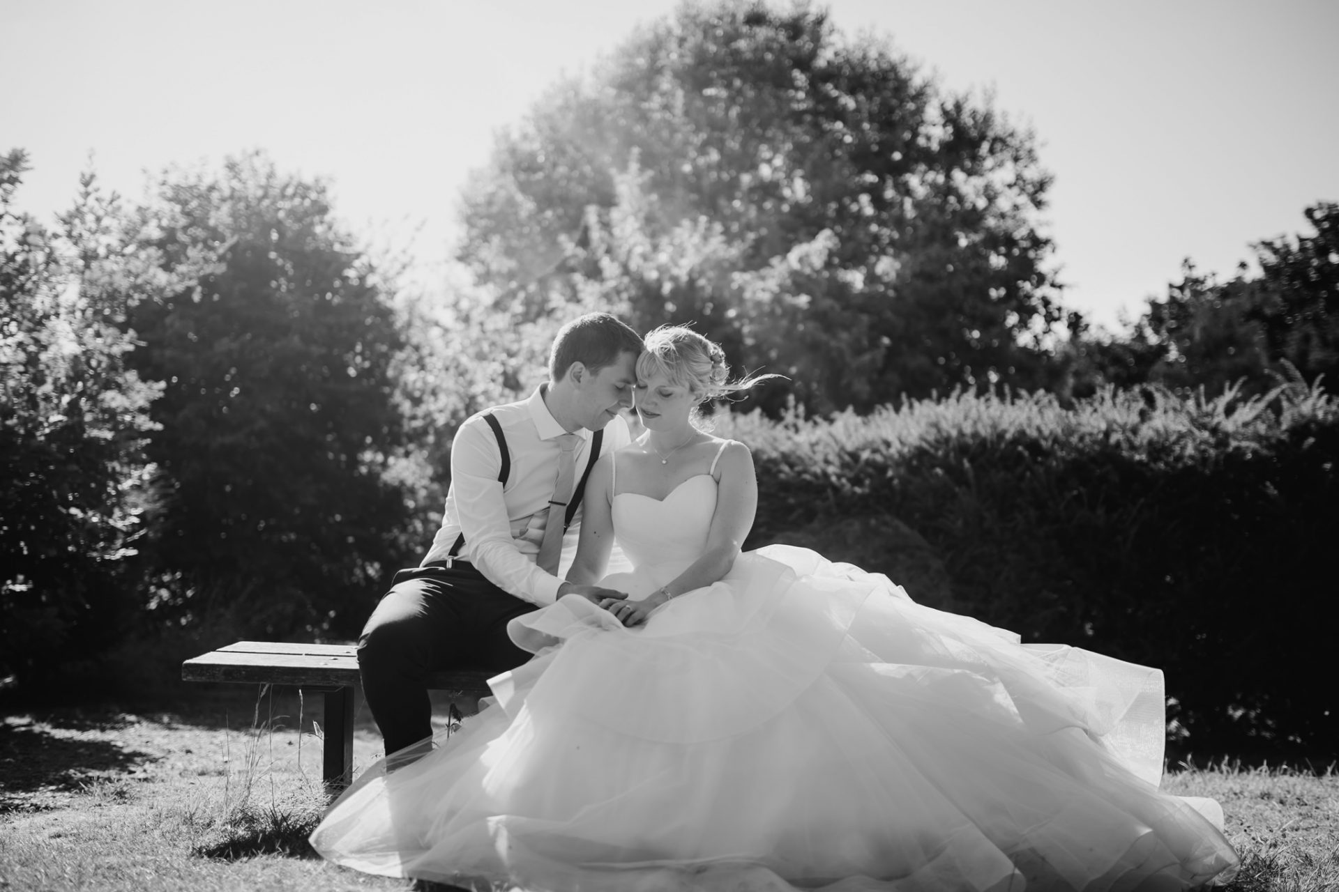 bride and groom sitting on a park bench