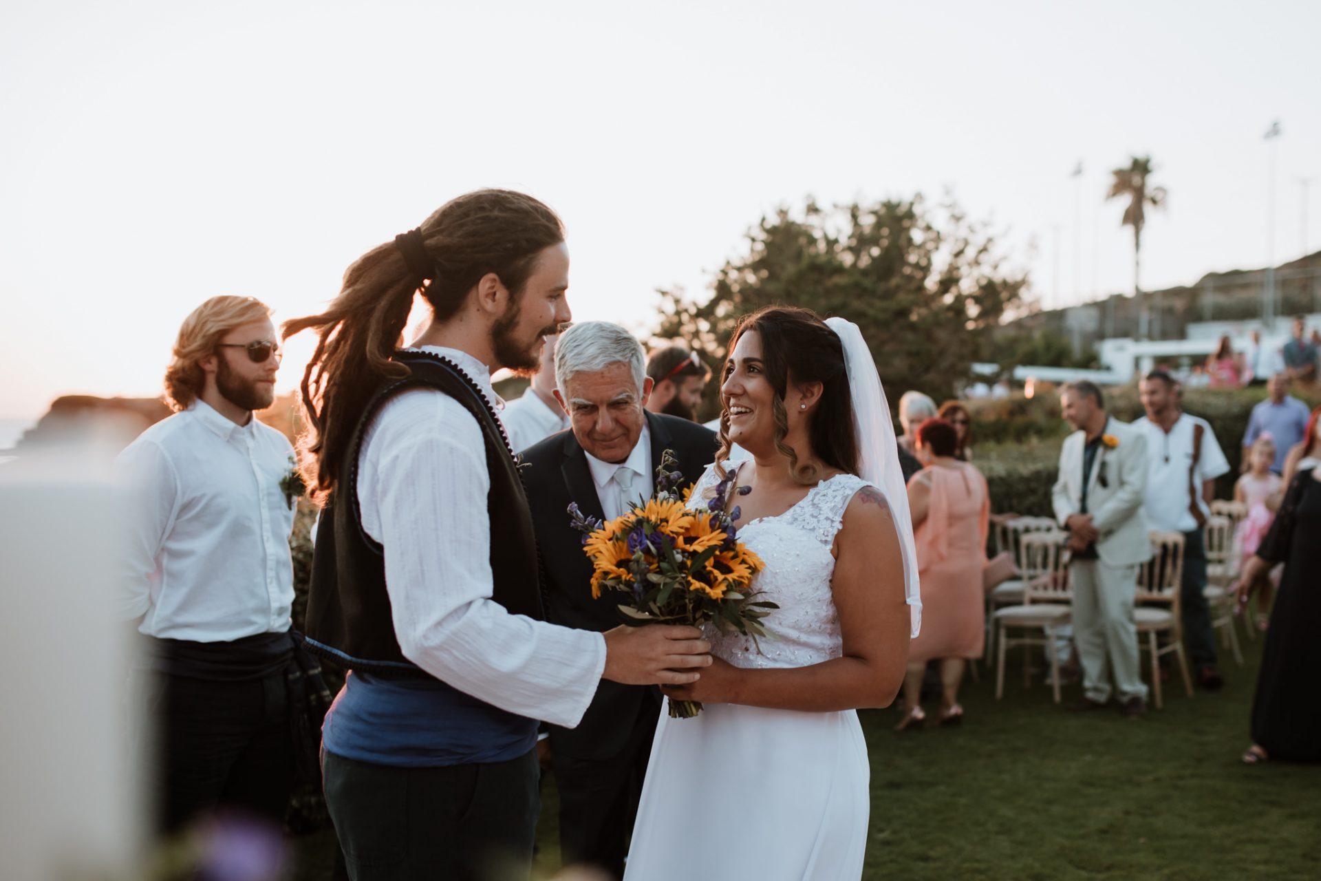 groom hands the bride the wedding bouquet
