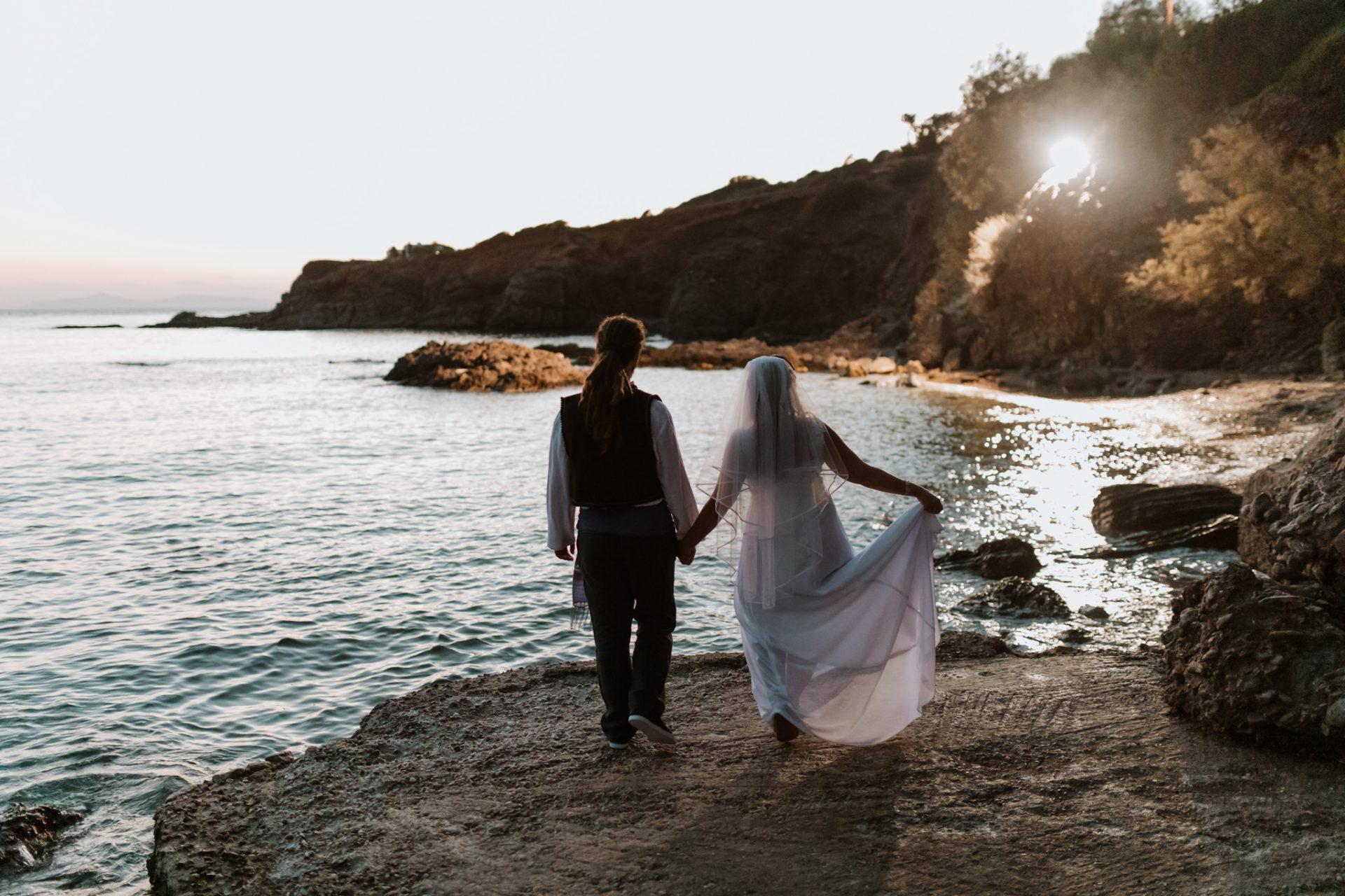 bride and groom walking towards sea