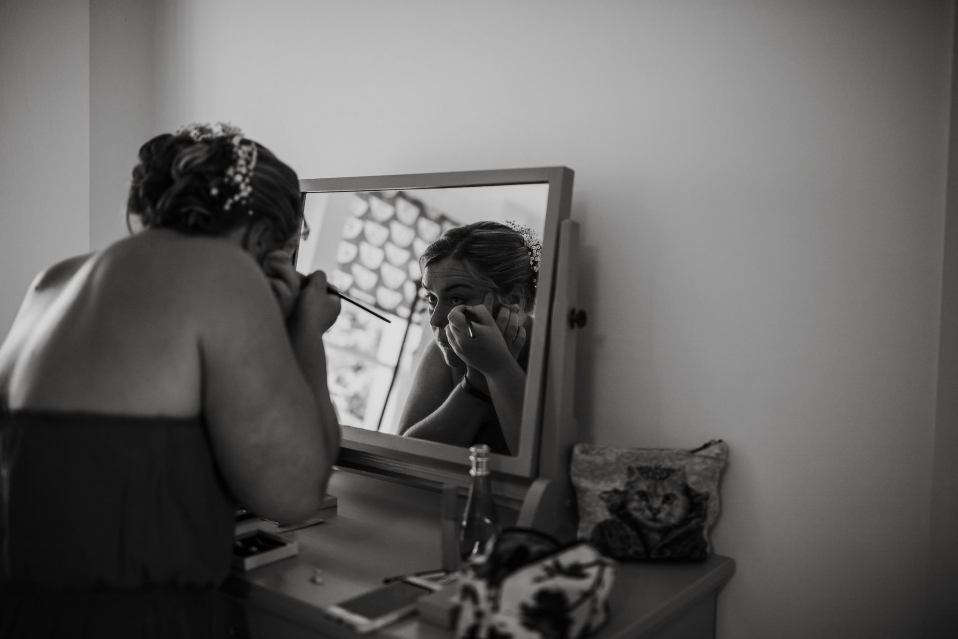 bridesmaid doing her makeup in the mirror