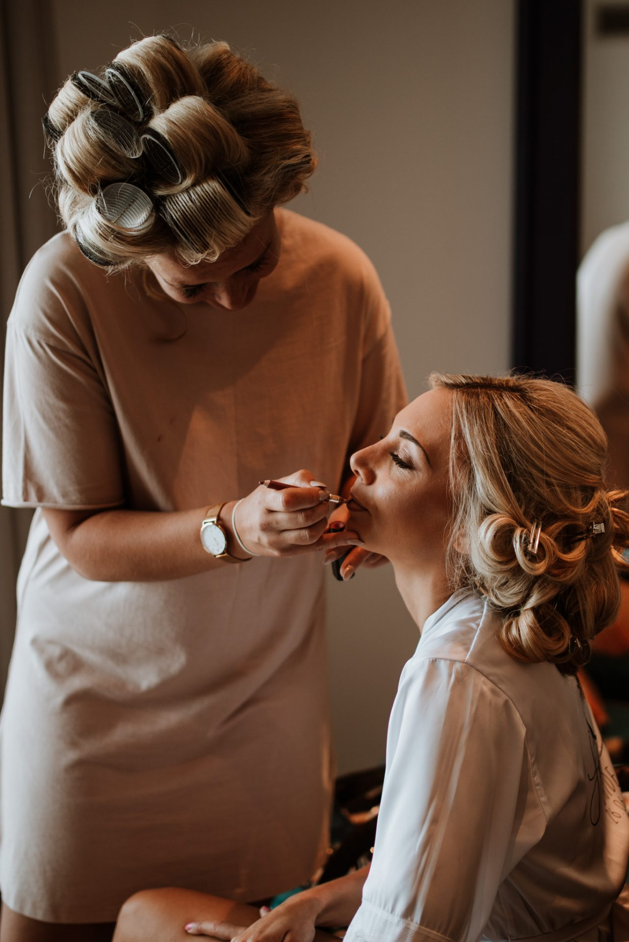 bride getting ready bridesmaid doing her make up