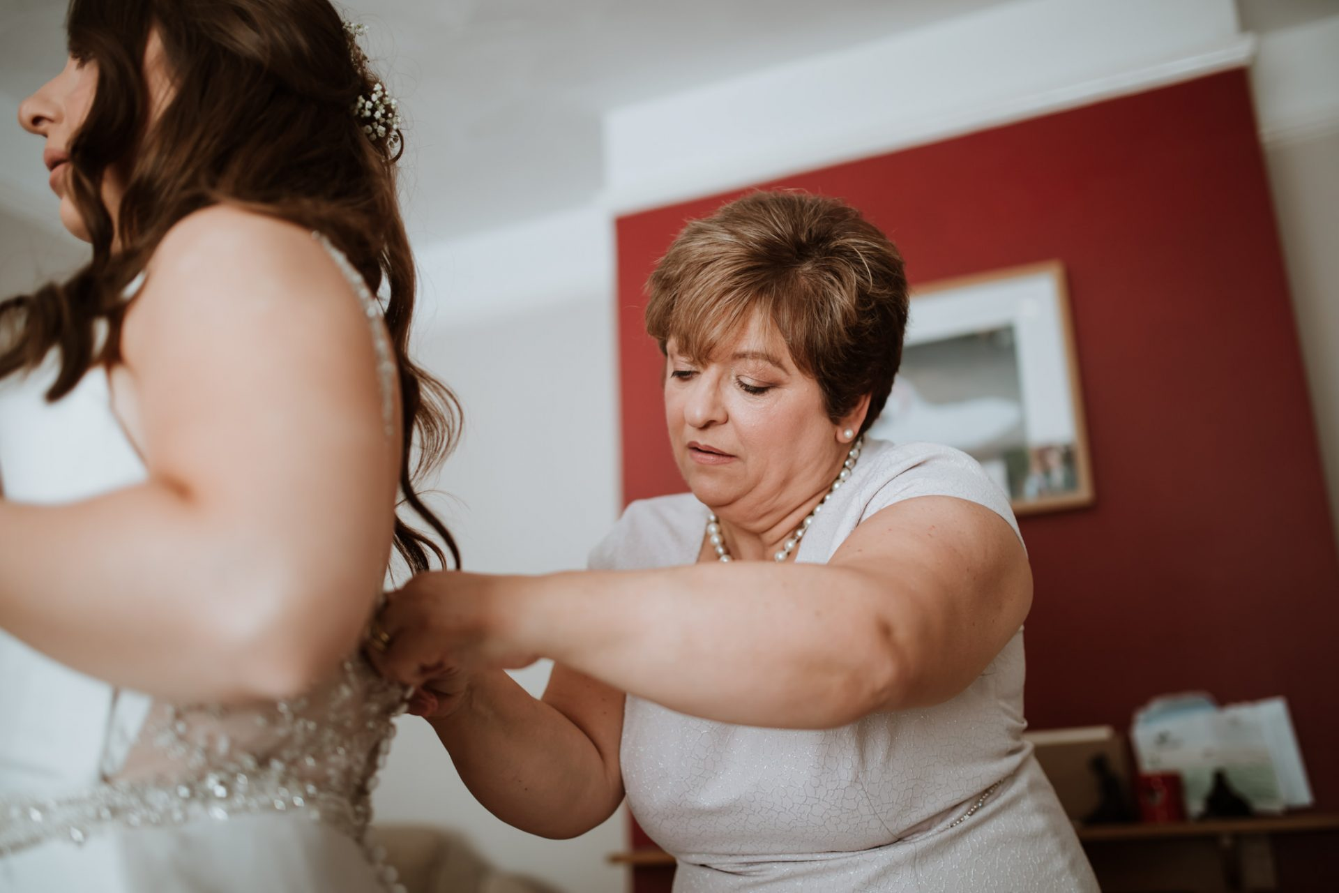 mother buttoning the bride in to her wedding dress