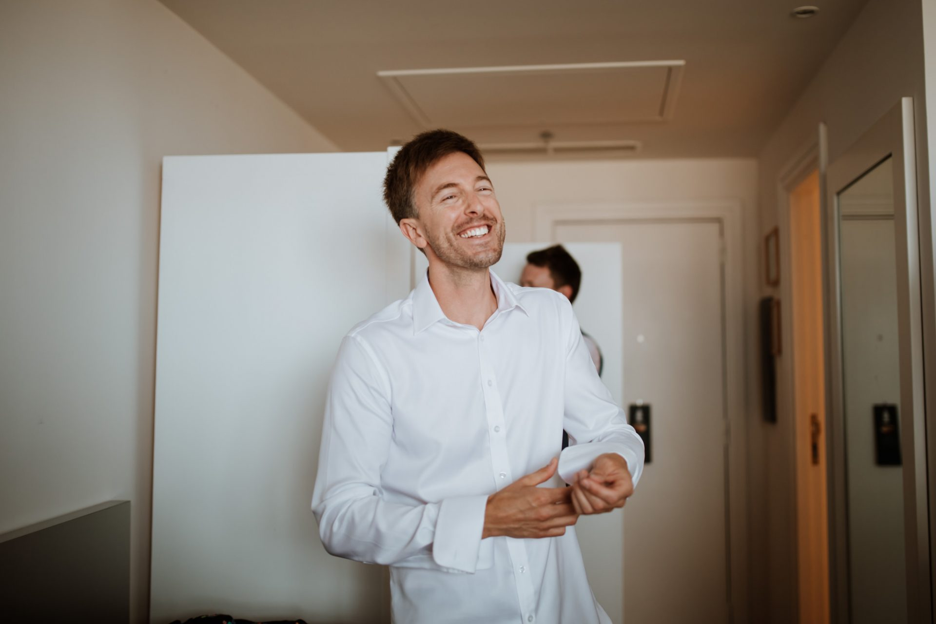 groom laughing as he puts on his shirt