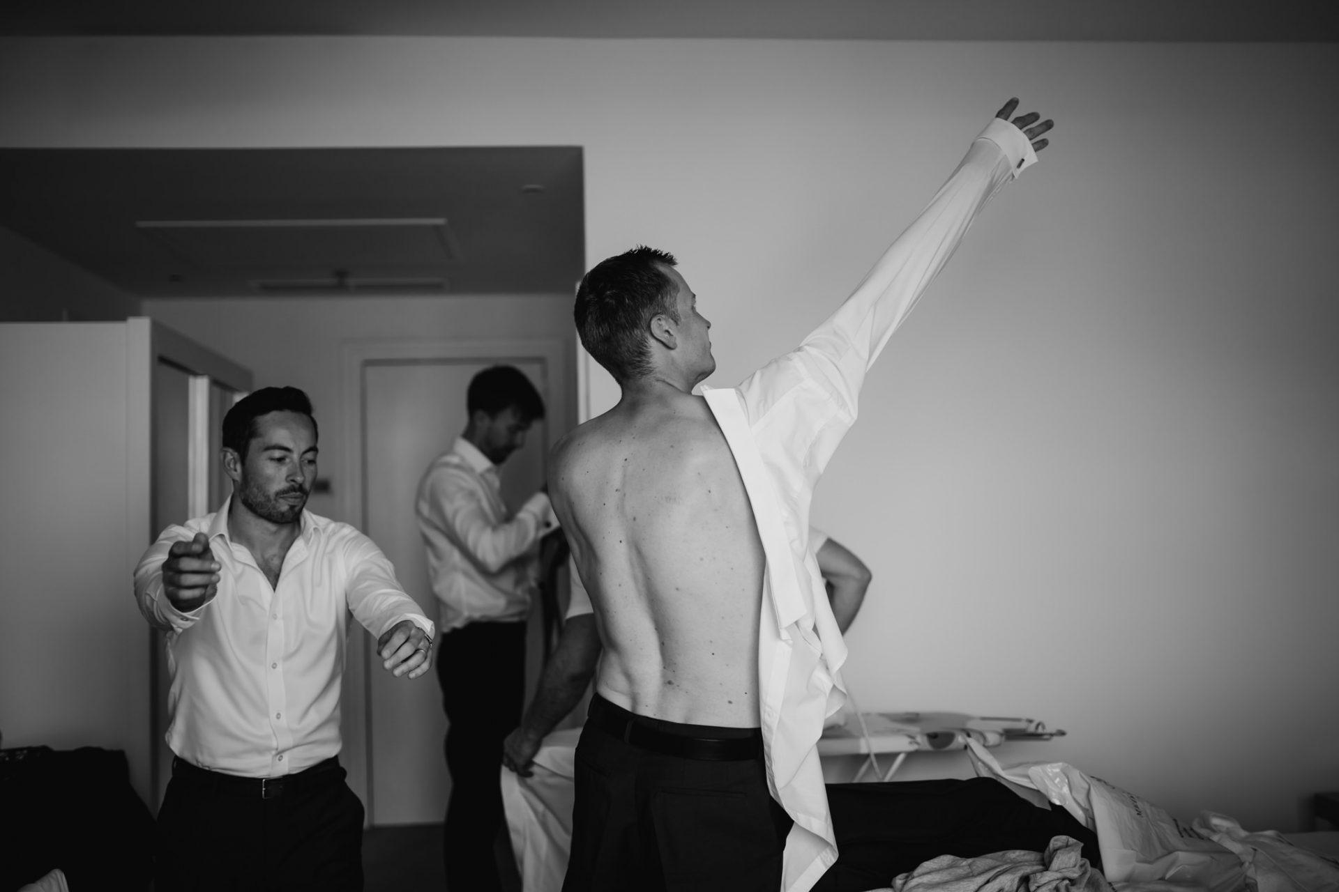 groomsmen putting on their shirts