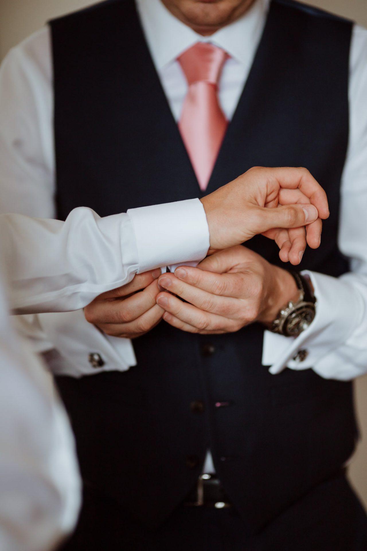 groomsman putting on the grooms cufflinks