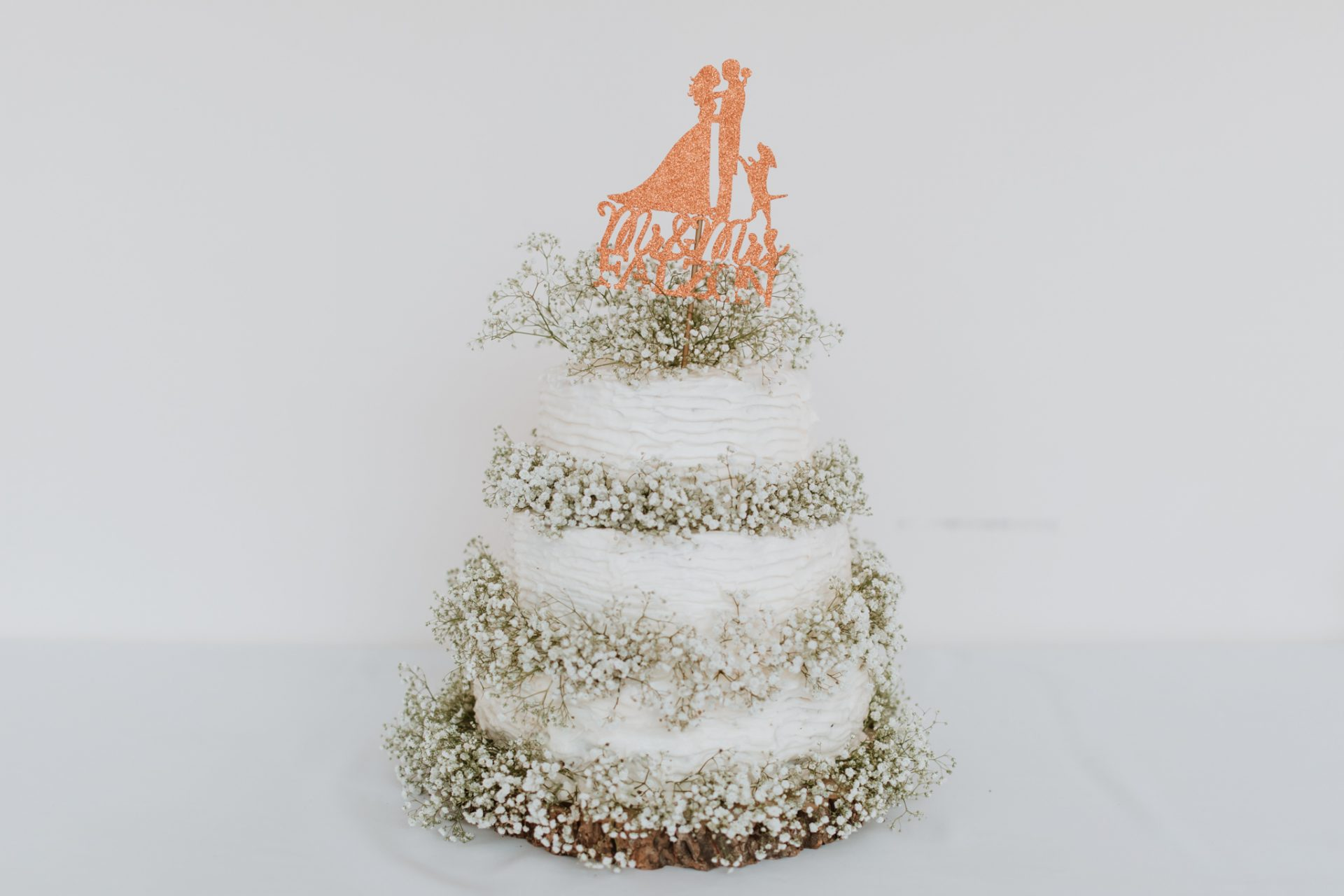 white weddings cake with babys breath and mr and mrs topper with a dog