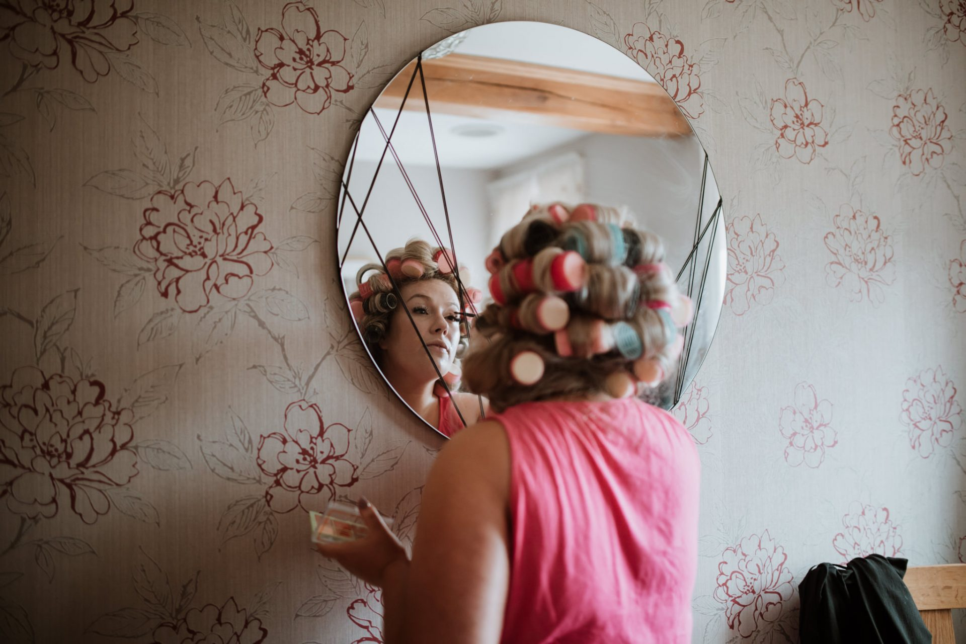 bridesmaid doing her make up in the mirror