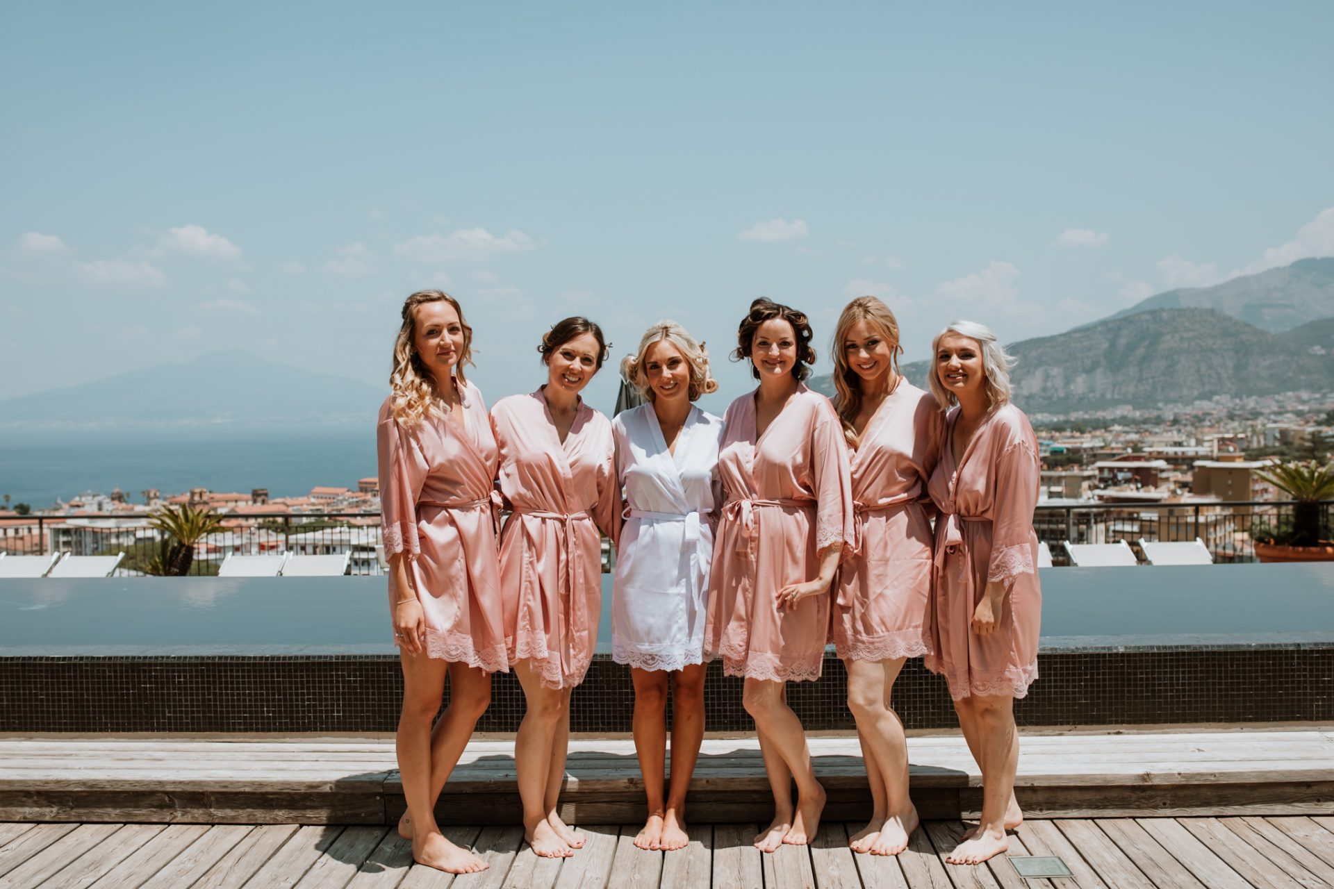 bridesmaids and bride on rooftop with views of sorrento
