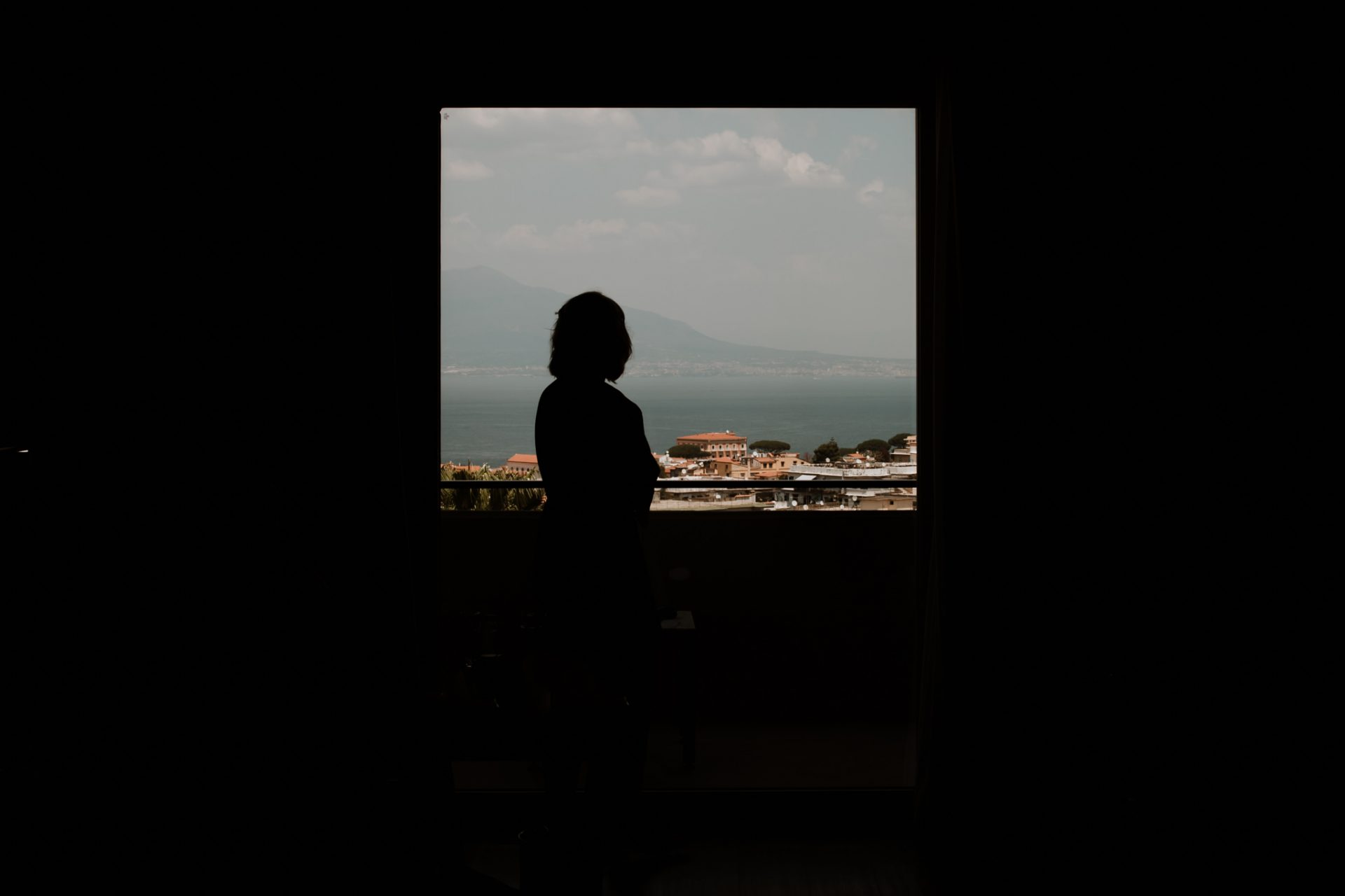 bridesmaid silhouetted in the window with a view of sorrento behind