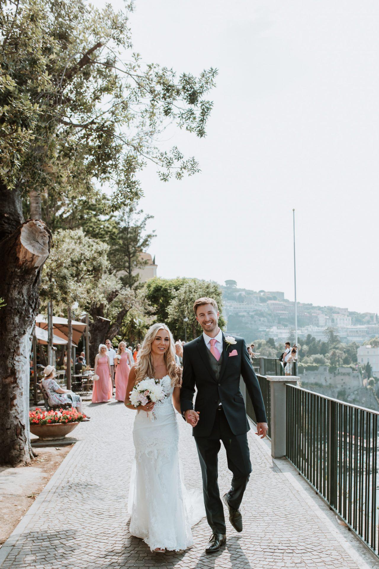 bride and groom walking along the coast sorrento