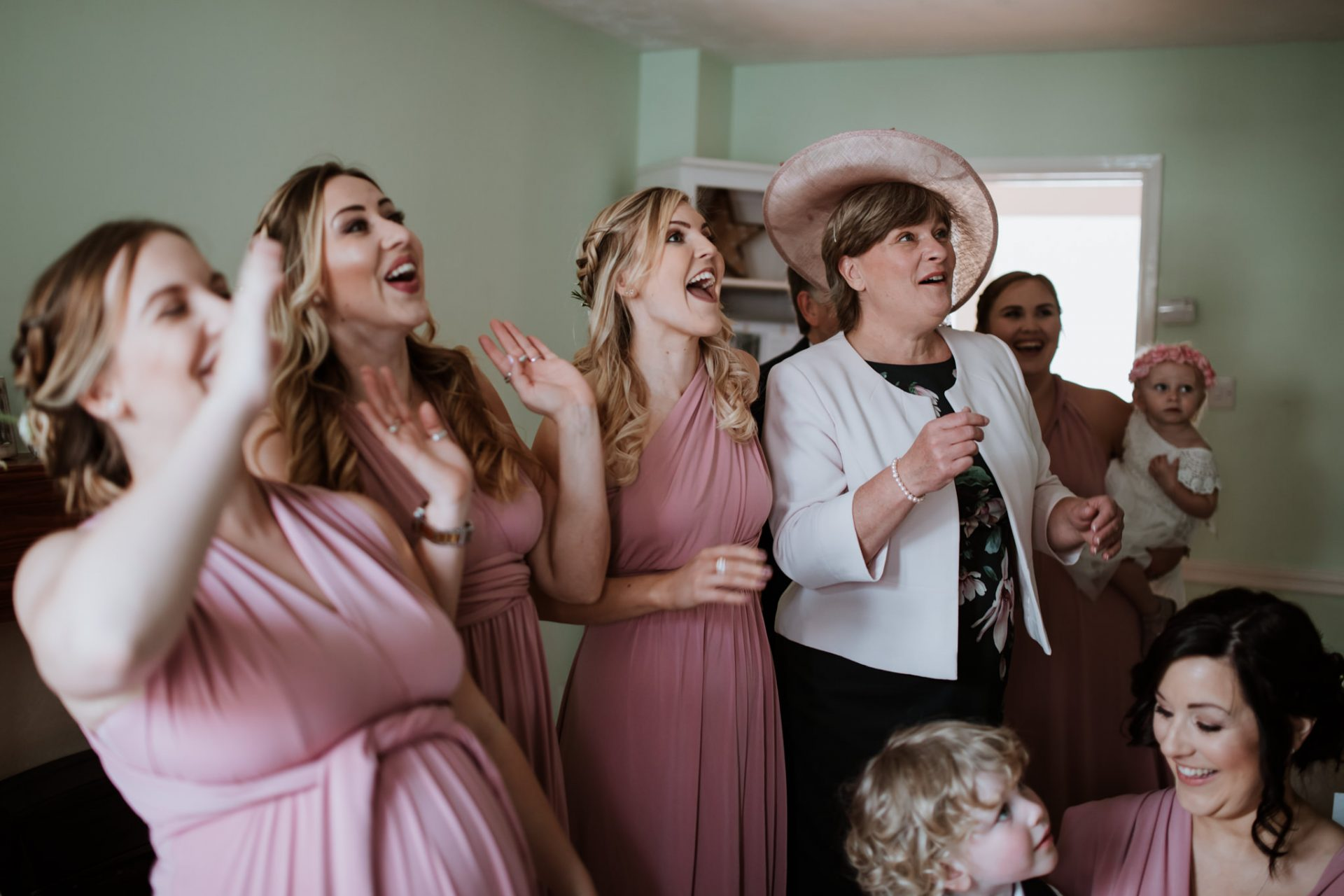 bridesmaid and parents of the bride react as they see the bride in her dress for the first time